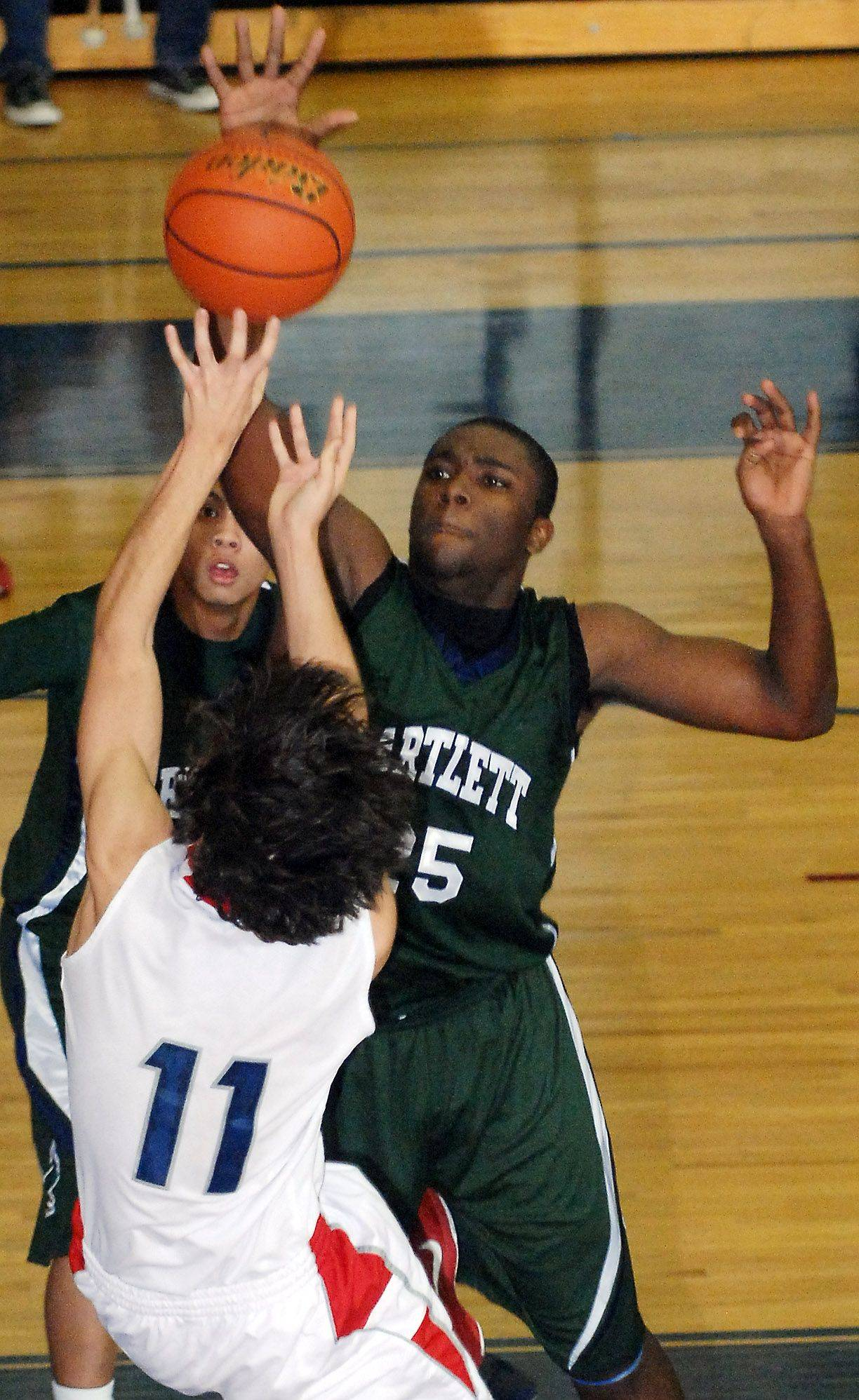 Bartlett's Lorenzo Mitchell defends a fallaway shot by South Elgin's Sammy Sutter.