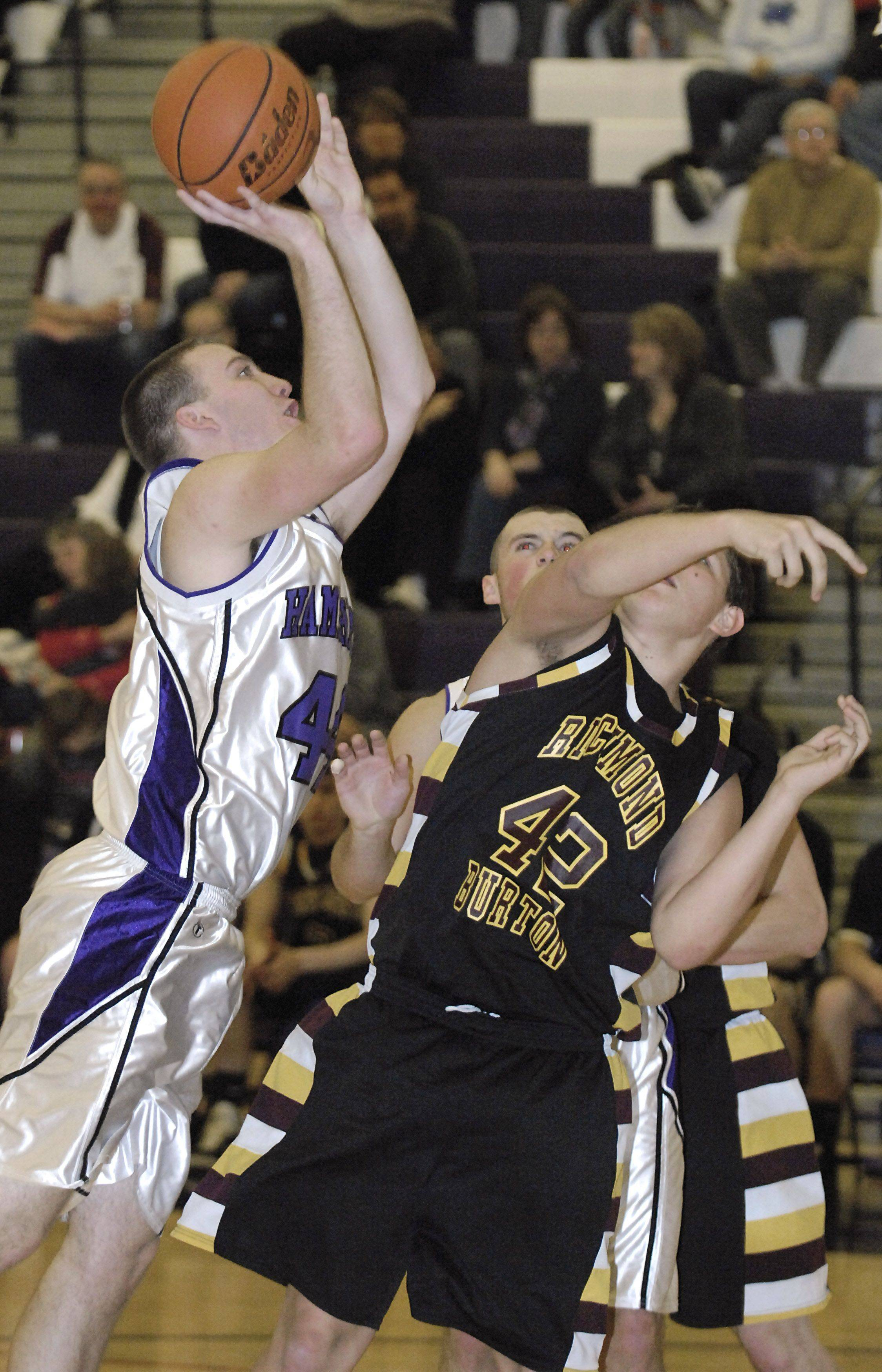 Hampshire's Tyler Watzlawick shoots over Richmond's Zach Rygiel in the second quarter on Saturday, January 8.