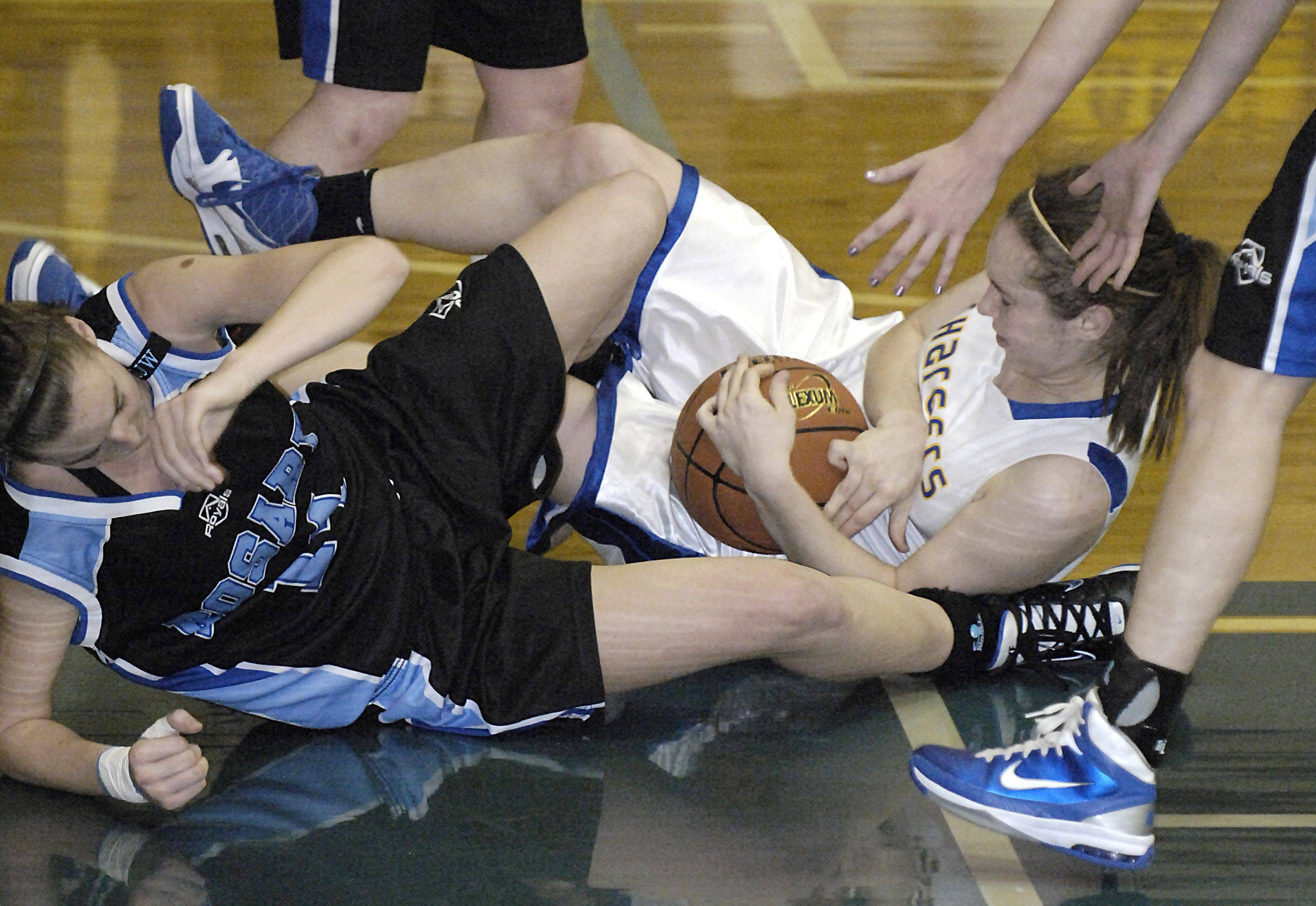 Rosary's Brittney Hutchinson and Aurora Central's Ashley Wilk tumble to the floor after wrestling for the ball in the fourth quarter .