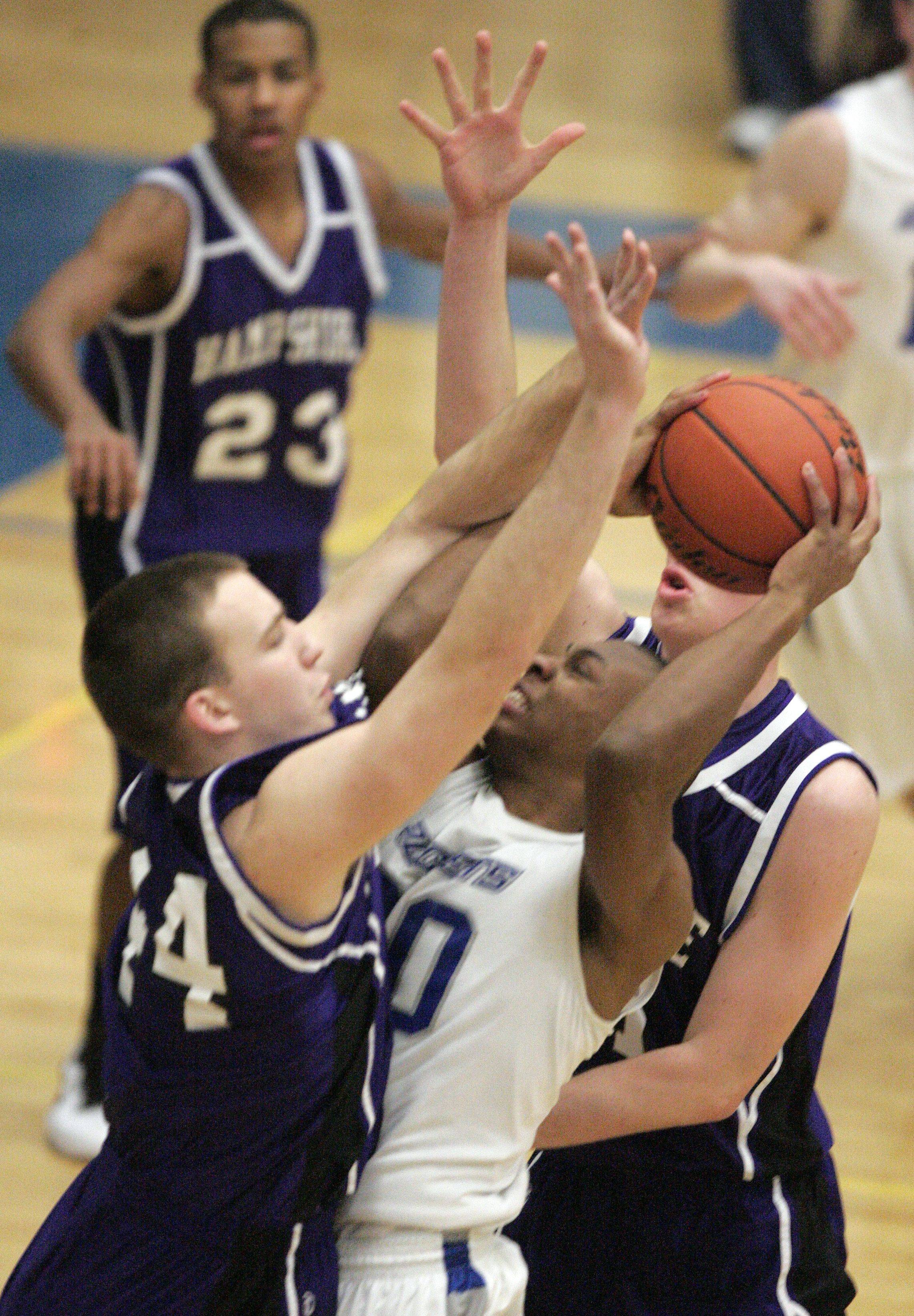 Burlington Central guard Ray Hunnicutt, 20, is sandwiched between Hampshire forward Tyler Watzlawick, left, and Hampshire center Shane Hernandez right Saturday.