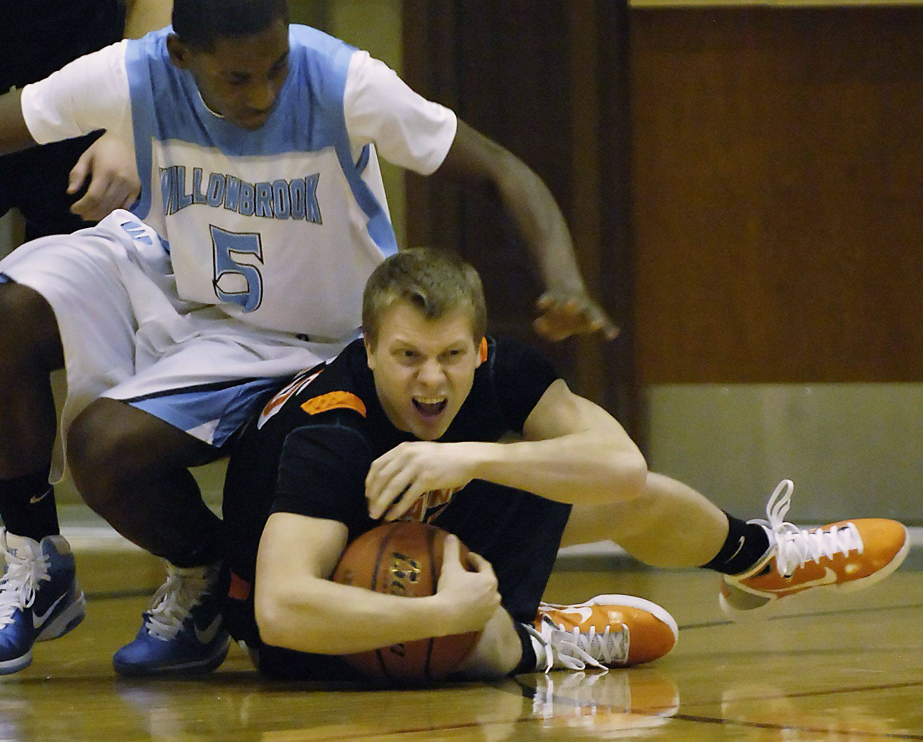 St. Charles East's Zach Zajicek protects the ball as Willowbrook's Tiger Greene plays defense.