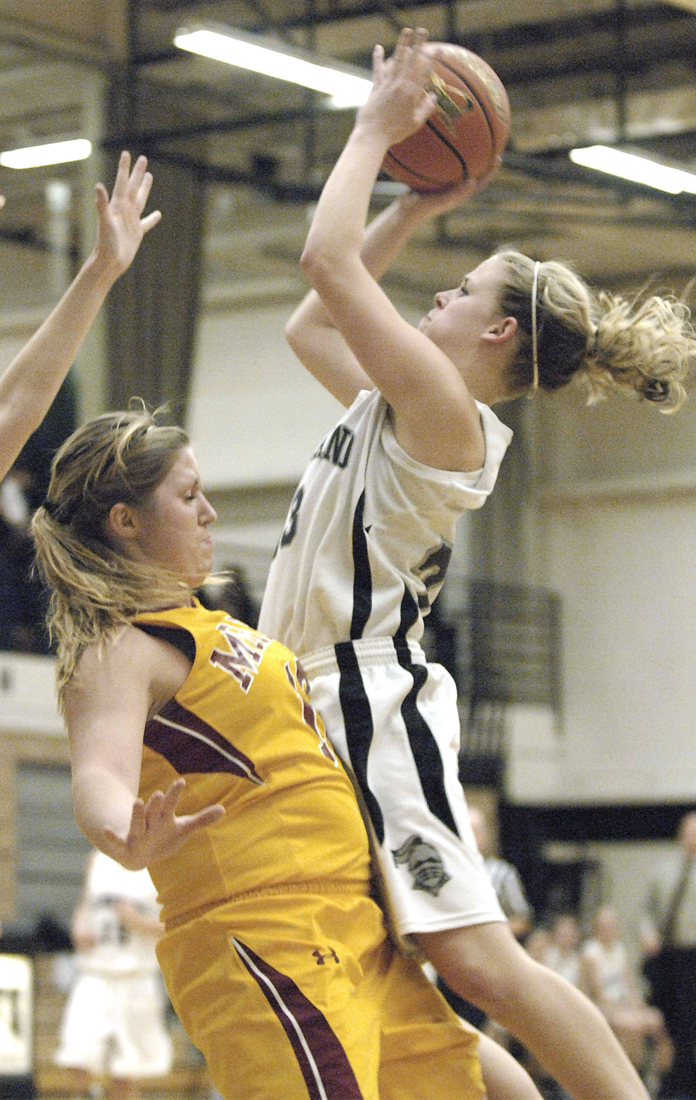 Kaneland's Tesa Alderman sinks a shot while colliding with Morris' Layney Miller in the first half.