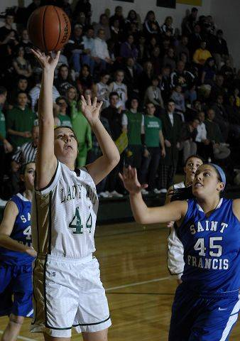 St. Edward's Madeline Kerr puts up a shot as St. Francis' Morgan Connelly rushes in to defend.
