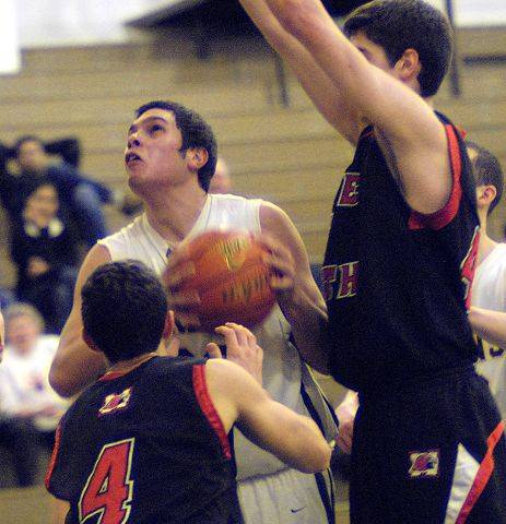 Bill Zars/bzars@dailyherald.comElk Grove's Kevin Morelos puts up a shot with tough defense from Maine South's Nick Calabrese and Matt Palucki Monday night at Elk Grove.