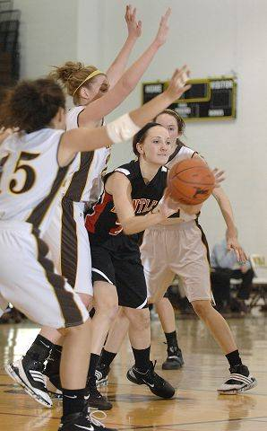 Huntley's Abbey Shaw passes out of a block by Jacobs' Payton Berg and Melanie Schwerdtmann in the third quarter.