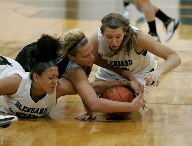 Left to right, Shanice Hayes, of Glenbard West, Jenna Dalton of Willowbrook and Cayla Herbst of Glenbard West all dive after a loose ball in girls basketball action Tuesday in Glen Ellyn.