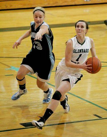 Bev Horne/bhorne@dailyherald.com Jessica Nolan, left, of Willowbrook defends as Bridget Flanagan of Glenbard West drives to the basket in girls basketball action Tuesday in Glen Ellyn.