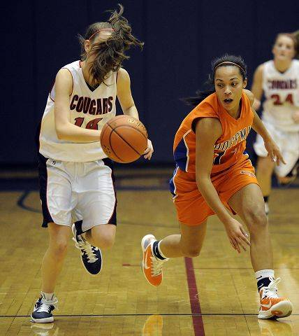 Conant's Alyssa Rawleigh gets blinded by her own hair as she chases down a loose ball with Hoffman Estates Jada Stotts in hot pursuit during the girls basketball game at Conant High School on Thursday.