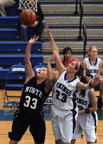 St. Charles North guard Taylor Russell has her shot altered by Geneva's Katelyn Allen during Thursday's game in Geneva.