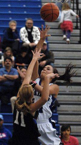Geneva's Kat Yelle scores over St. Charles North guard Megan Booe during Thursday's game in Geneva.
