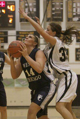 West Chicago Center, Mary Connolly is fouled while trying as she moves to the basket by Glenbard North's Carson Jones.
