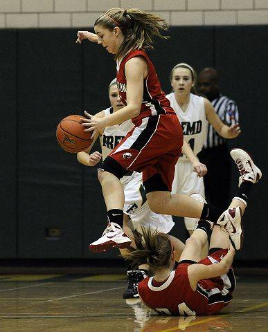 Barrington's Brooke Chandor does some fancy footwork as she goes airborne jumping over a fallen teammate .