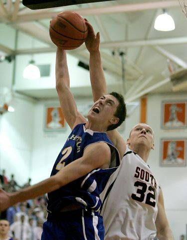 Sam Otto of Wheaton North, left, tries to make a basket, but Jason Schuman of Wheaton Warenville South hits the ball away.