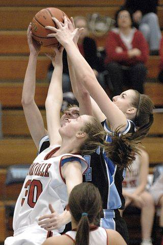 Rosary's Breann Maryanski and Brittney Hutchinson both go for a rebound during the Royals' 64-56 overtime win in the Class 3A IMSA regional Tuesday night.