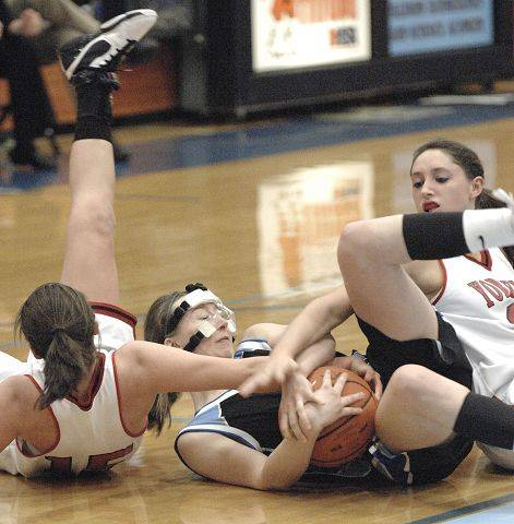 Rosary's Mary Wentworth, center, wrestles for the ball with Yorkville's Jordann (cq) Dhuse and Jenny Taptich in regional game on Tuesday, February 15.
