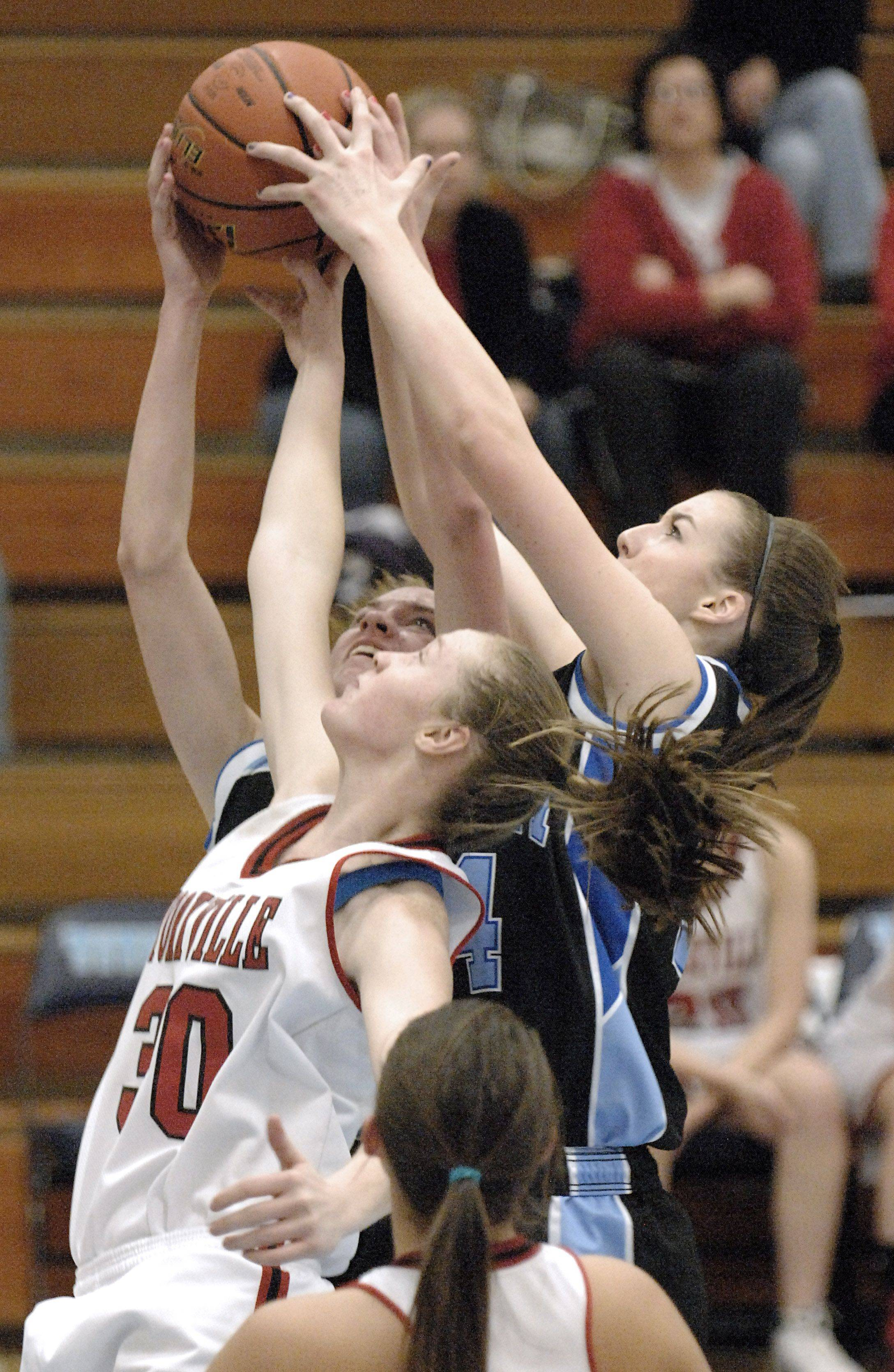 Rosary's Breann Maryanski and Brittney Hutchinson grab for a rebound under the hoop and away from Yorkville's Devin Turner in the second quarter.