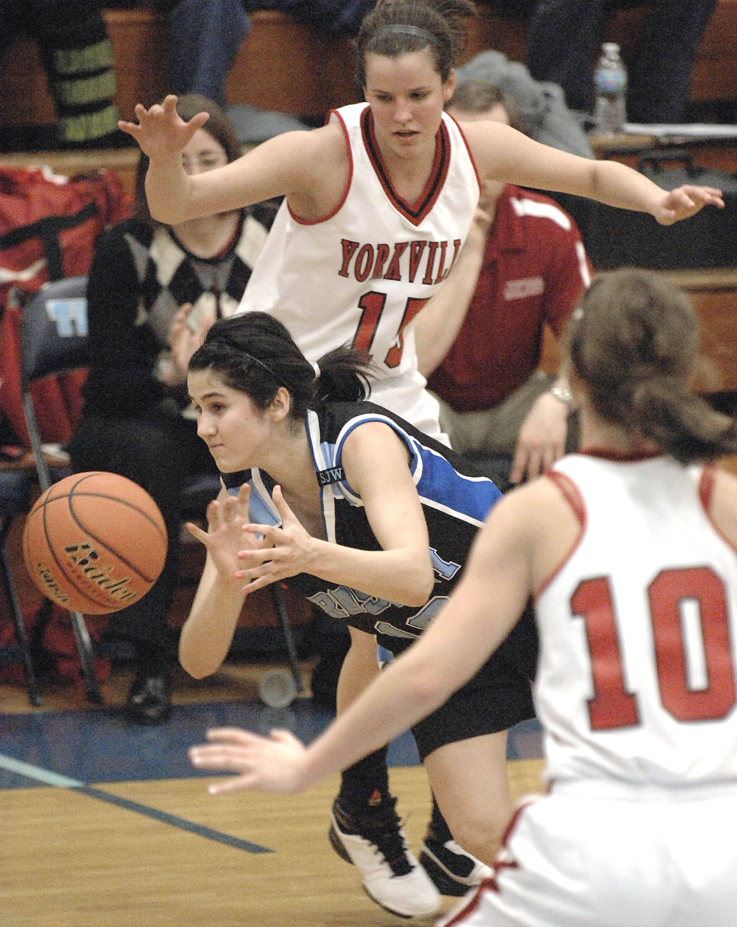 Rosary's Brenda Rocha loses control of the ball while on the way to the hoop with Yorkville's Jordann Dhuse and Cara Schlichting.