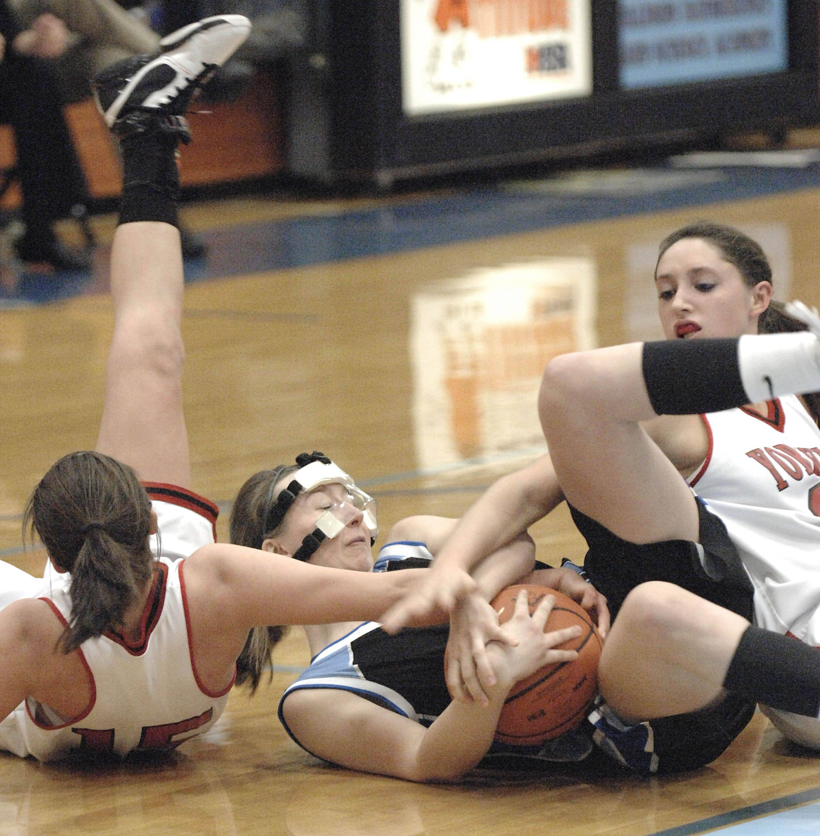 Rosary's Mary Wentworth, center, wrestles for the ball with Yorkville's Jordann Dhuse and Jenny Taptich .