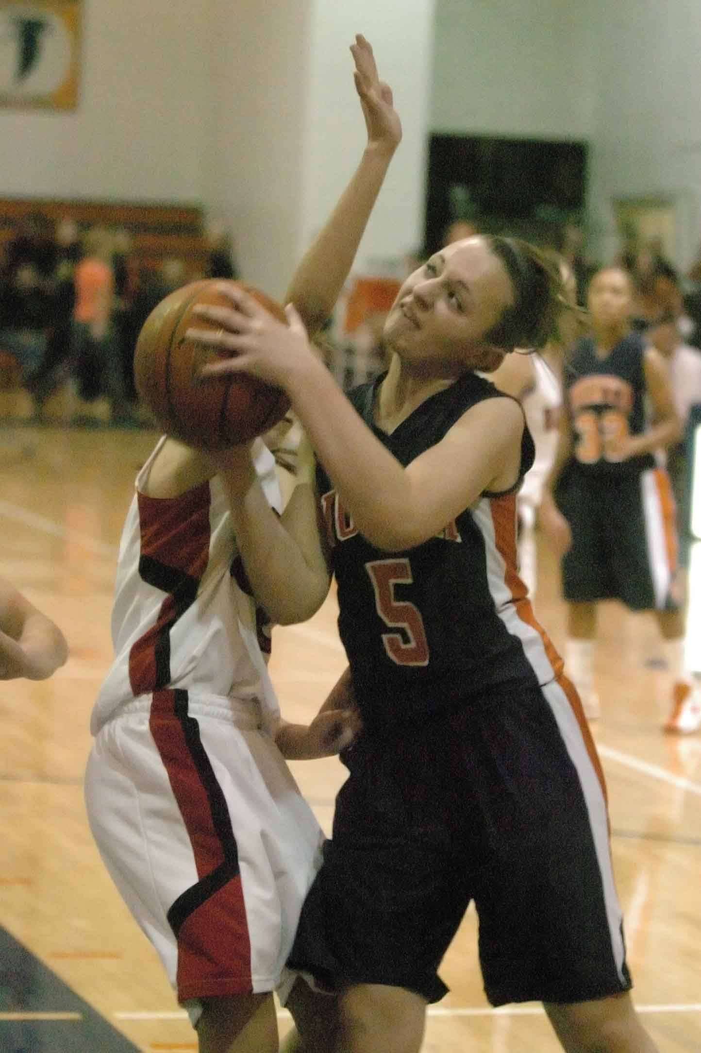 Jenna Jatczak of Naperville North tries to put up a shot against Benet.