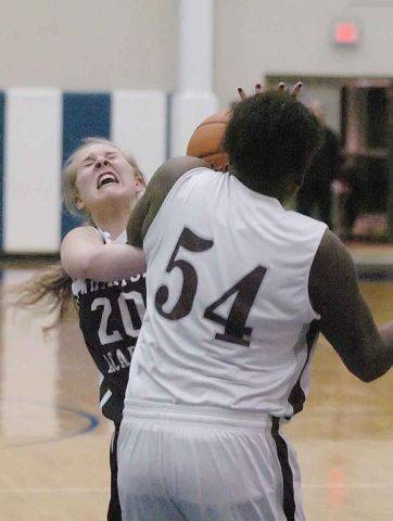 Sarah Drury of Wheaton Academy and Tianna Brown of Montini struggle for control of the ball.