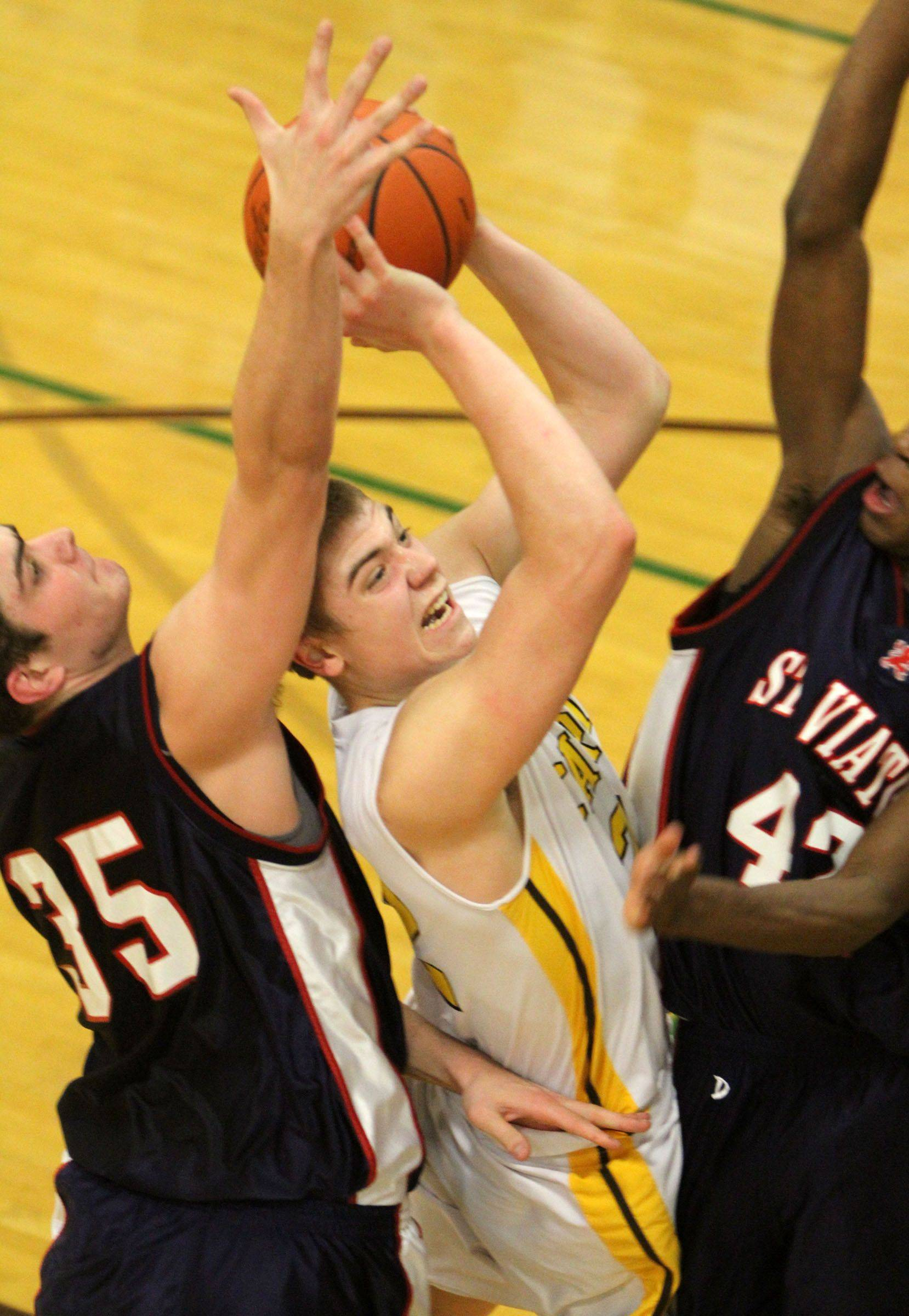 Carmel's Dan Mooney shoots while sandwiched between St. Viator defenders Chris Myjak, right, and Ore Arogundade.