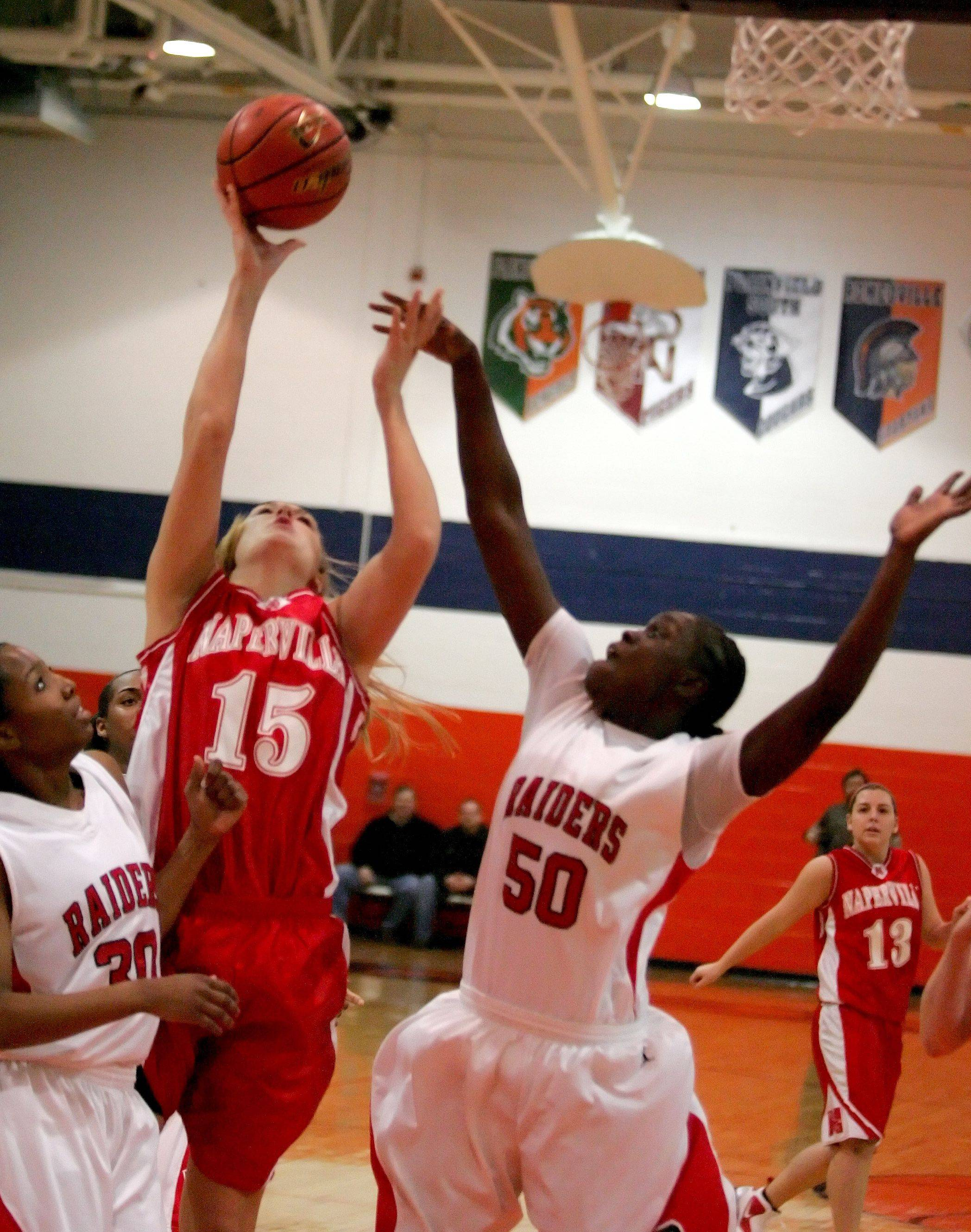 Victoria Towbridge of Naperville Central tries to make a basket as Bolingbrook's Cabriana Capers, right, defends on Monday night in Romeville.
