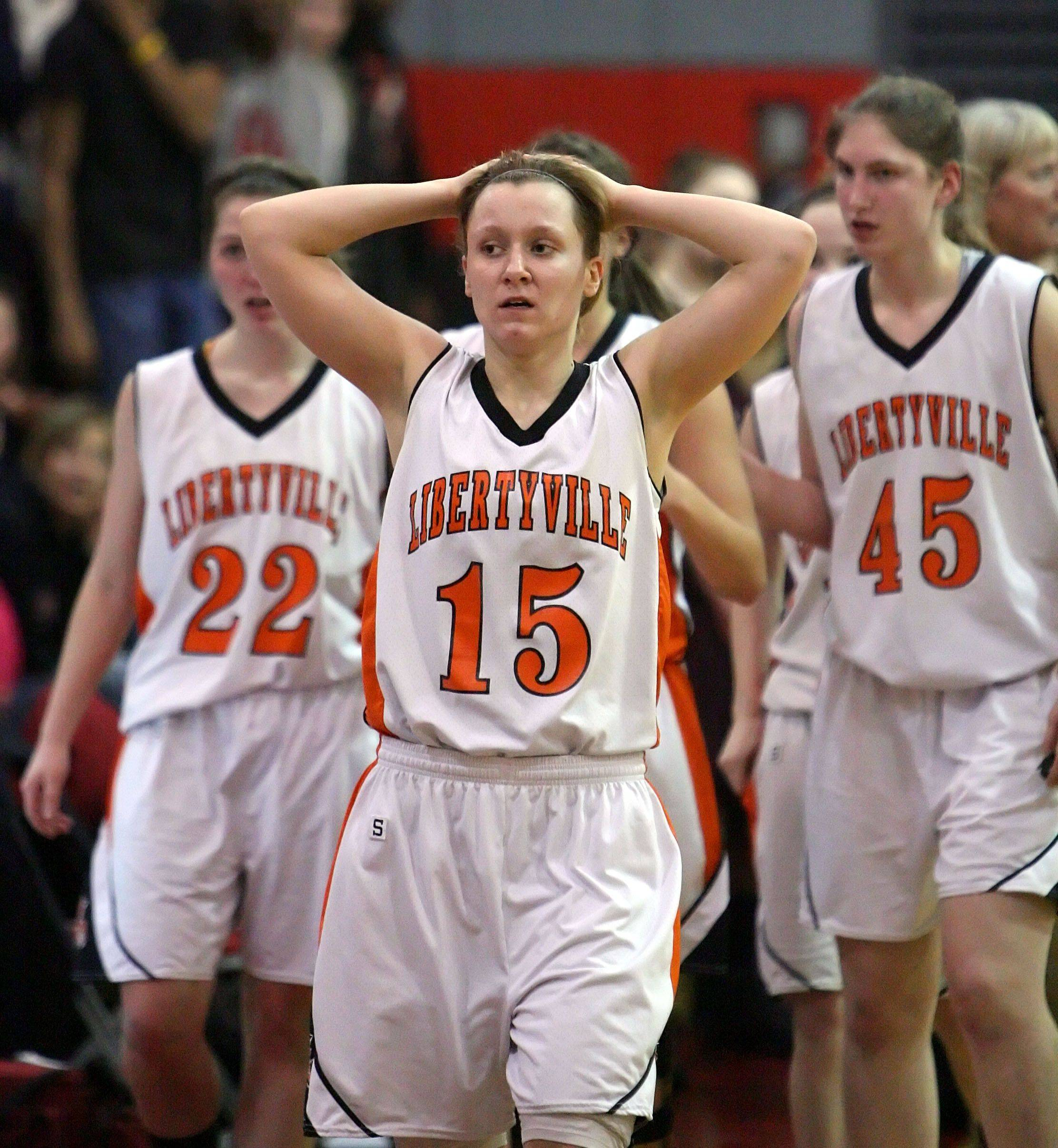 Libertyville's, from left, Olivia Wilcox, Alex Haley and Nicole Kruckman walk off the basketball court stunned after losing to Zion-Benton.