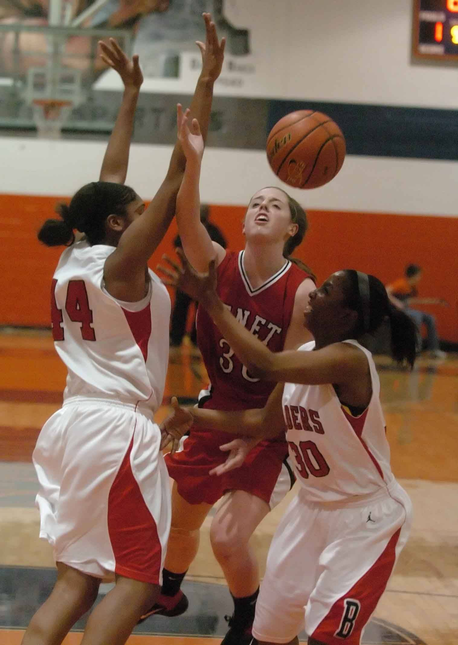 Ashley Veselik of Benet Academy puts up a shot while Morgan Tuck and Kierra Ray of Bolingbrook play defense.
