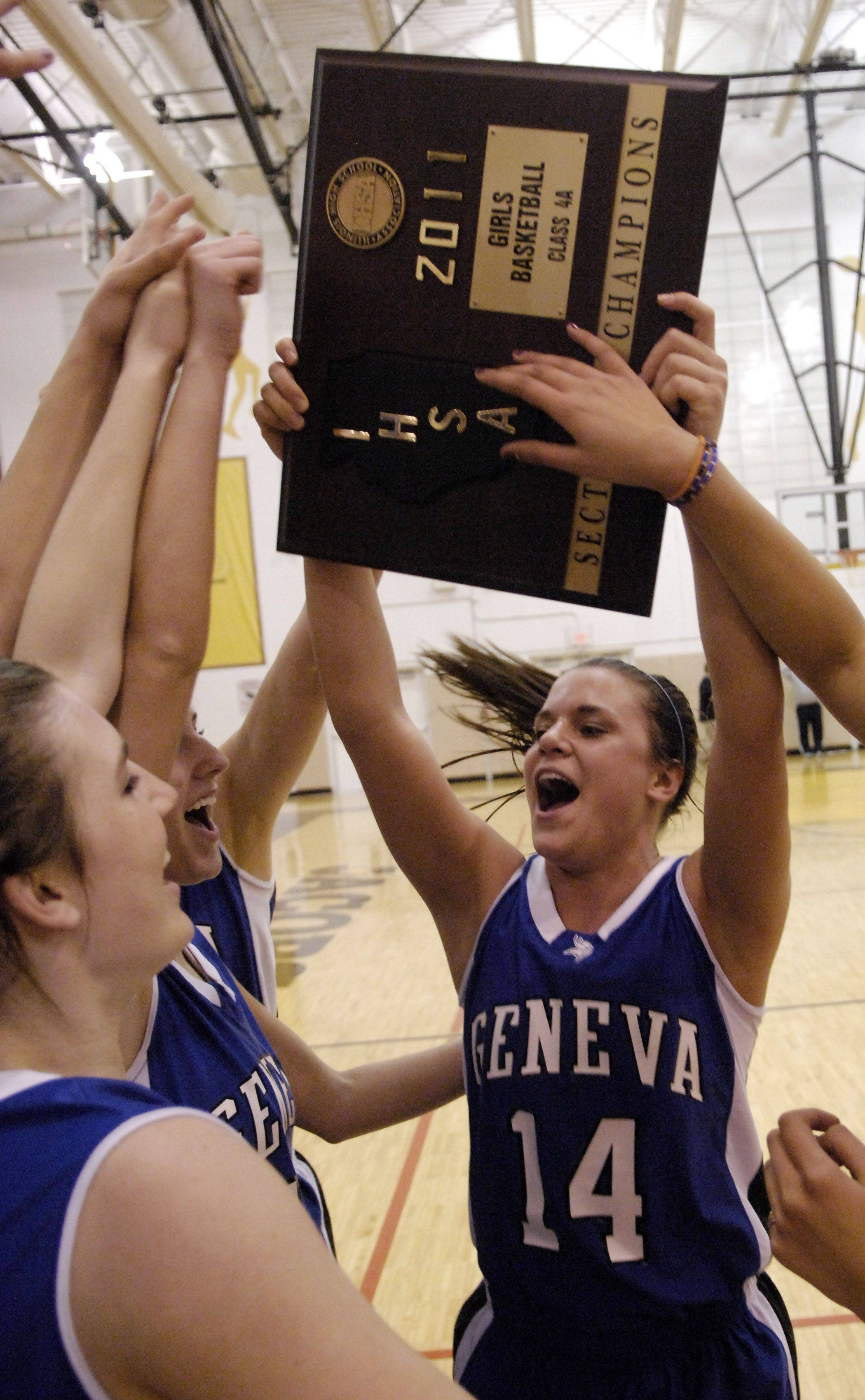 Geneva's Kat Yelle hoists up the sectional championship plaque following their win over Cary-Grove .