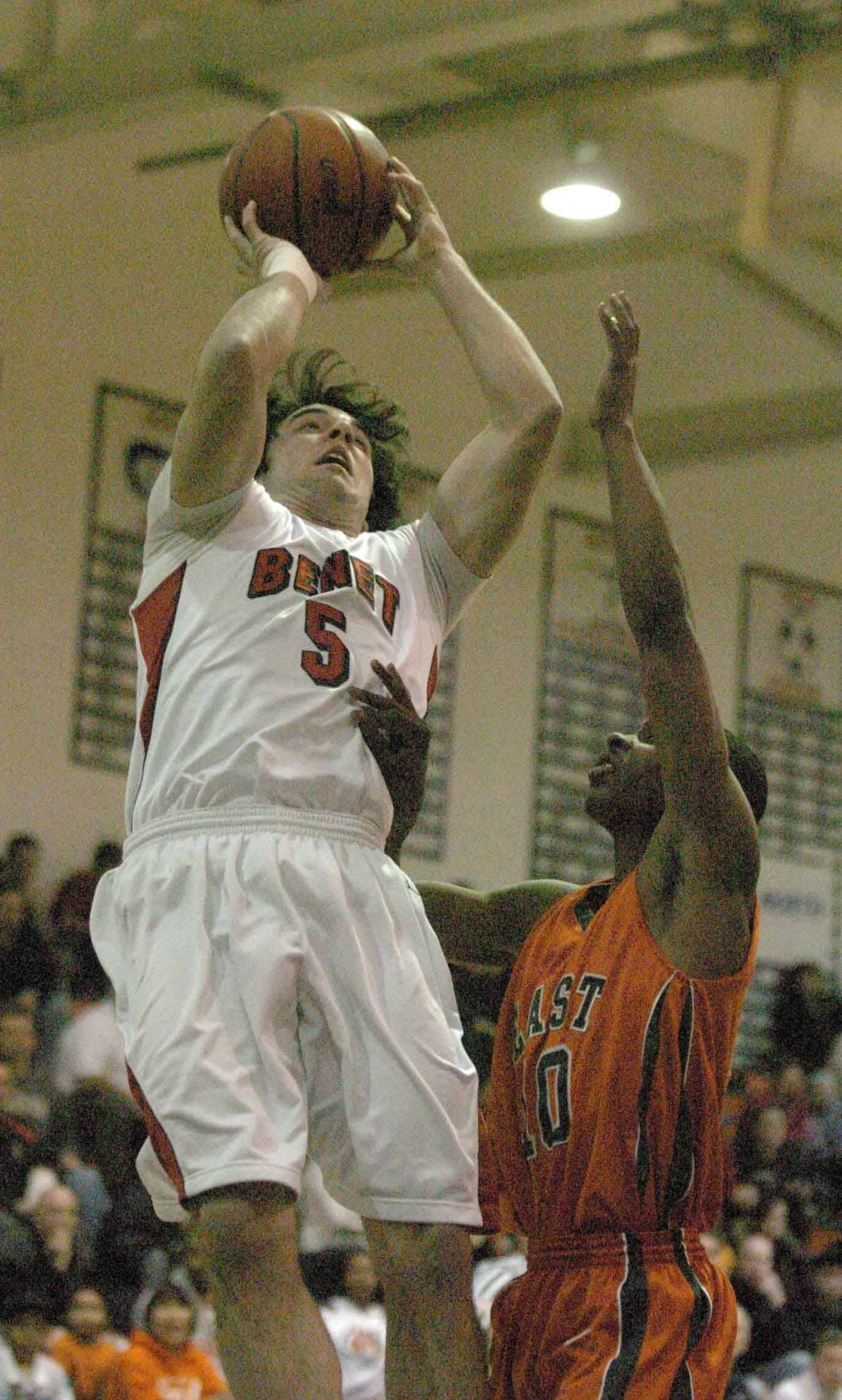 Pat Boyle of Benet Academy takes a shot over Jawan Straughter of Plainfield East.