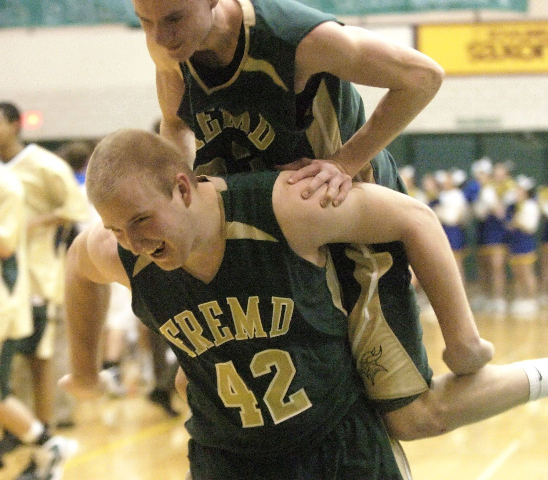 Fremd's Zach Monaghan jumps on the back of teammate Jack Konopka after defeating Lake Forest in the regional final Friday.