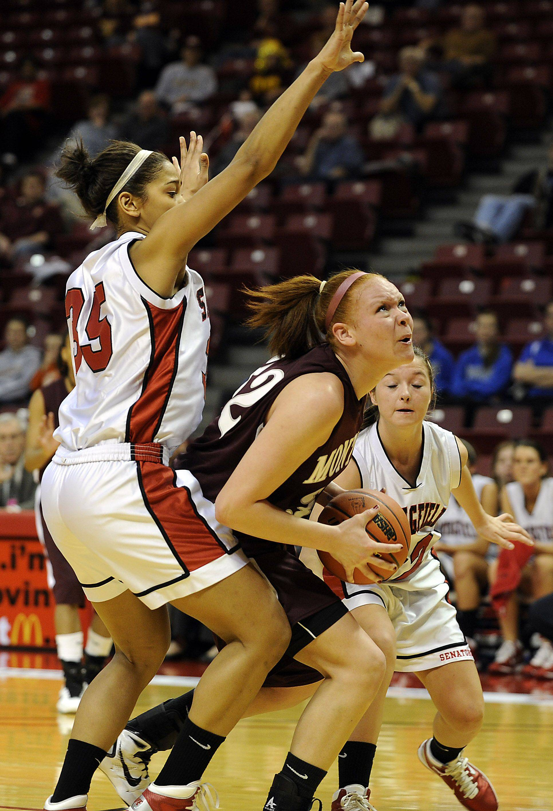 Montini's Whitney Adams plows through Springfield's defense of Amber Cason in the first half of girls basketball action at Redbird Arena on Friday.