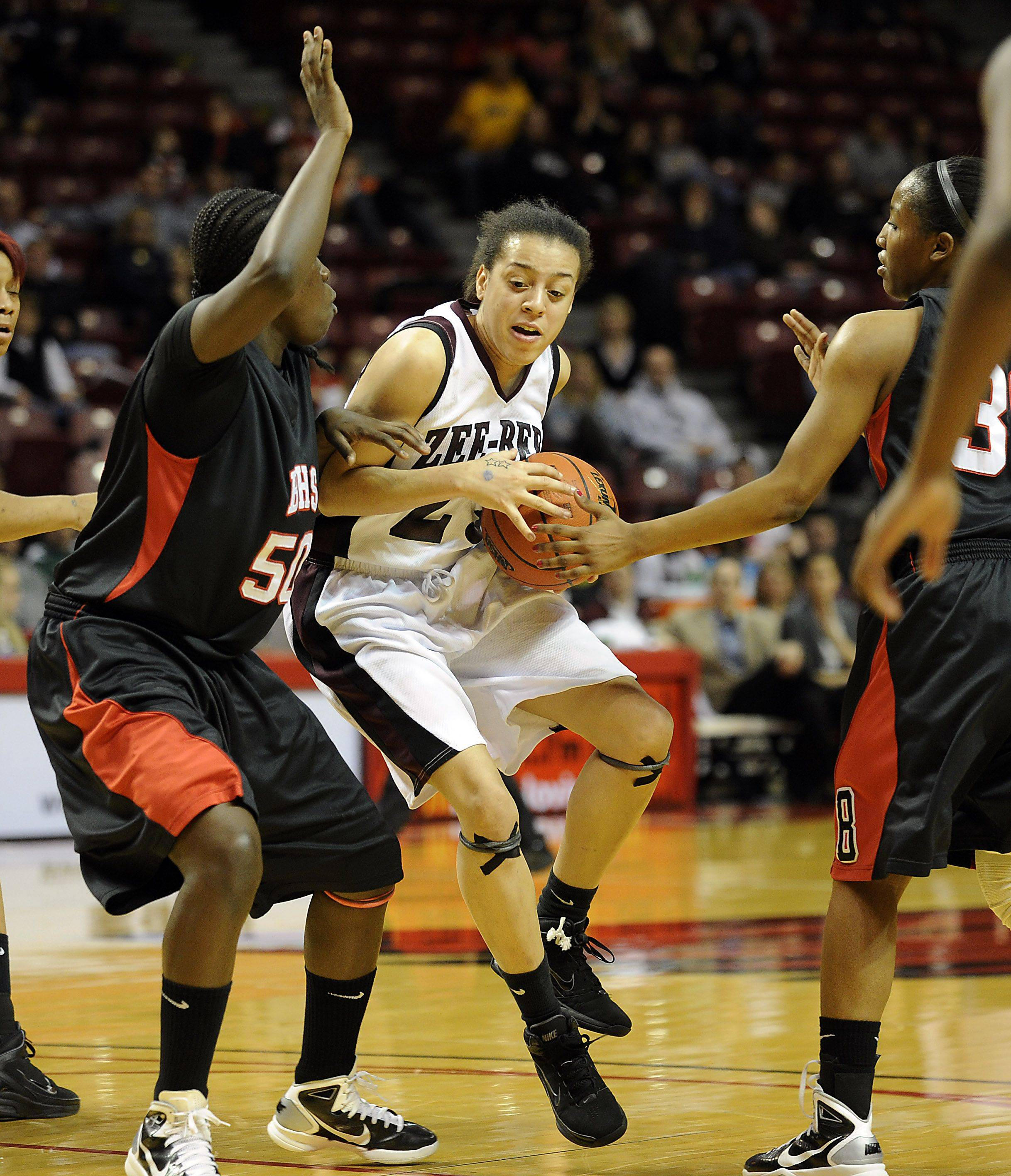 Zion-Benton's Juanita Robinson is called for traveling as she drives the lane as Bolingbrook's Cabriana Capers and teammate Kierra Ray provide strong defense in the girls Class 4A Girls Basketball Tournament at the Redbird Arena in Normal on Saturday.