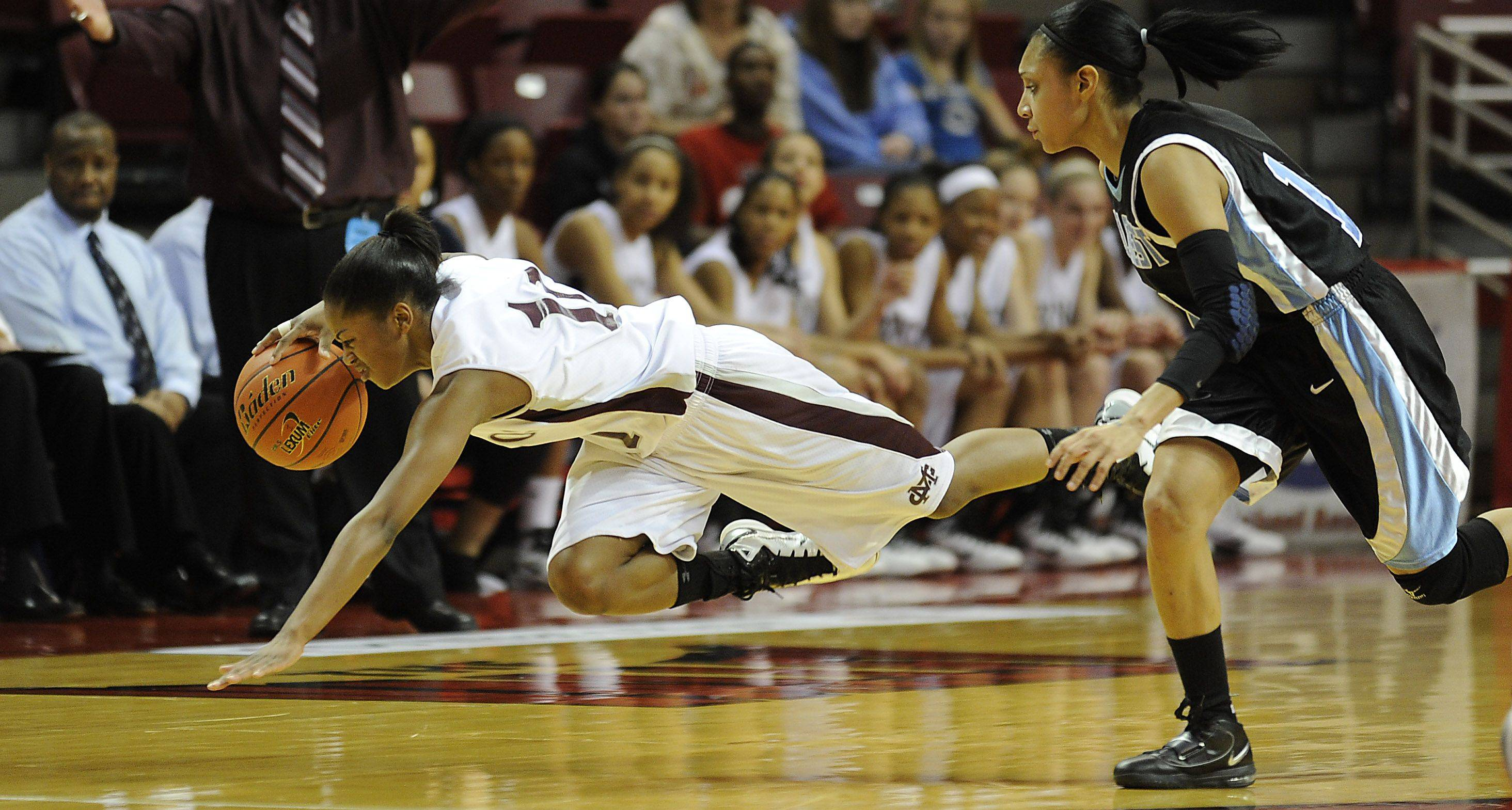 Montini's Whitney Holloway gets tripped up by Hillcrest's Karlisa Harris in the first half of Saturday's game in Normal.
