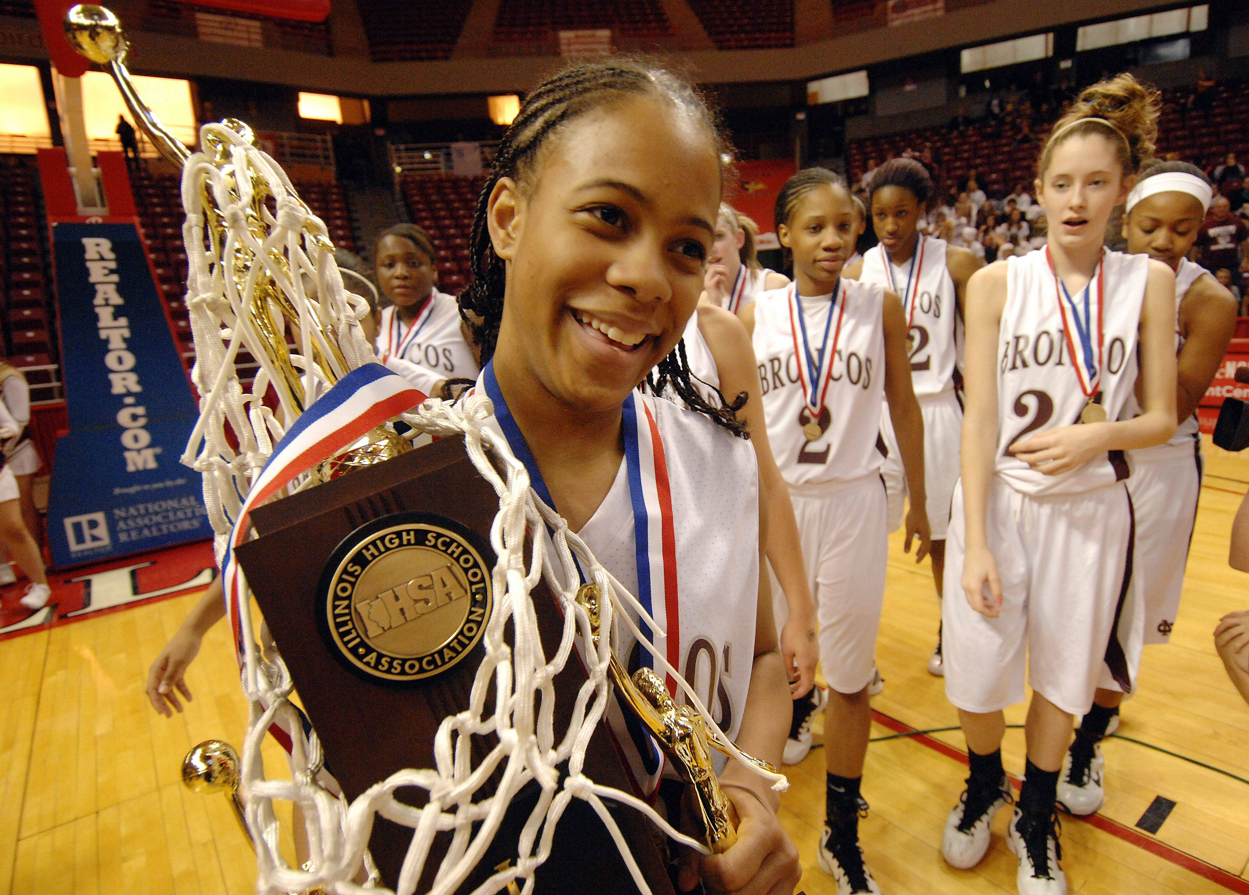 Montini's Kiki Wilson carries the trophy after their victory over Hillcrest at Redbird Arena in Normal.