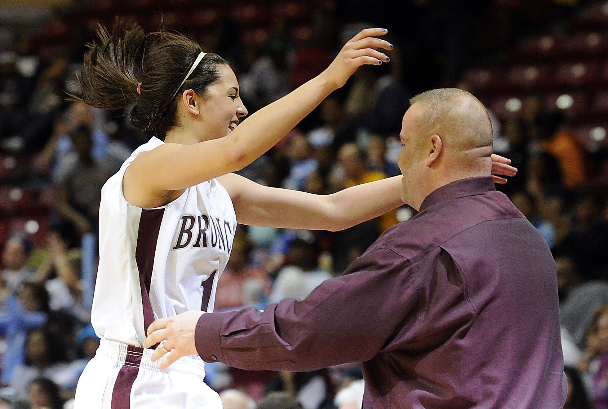 Montini's Kasey Reaber jumps for joy into the arms of coach Jason Nichols after winning the Class 3A title Saturday.