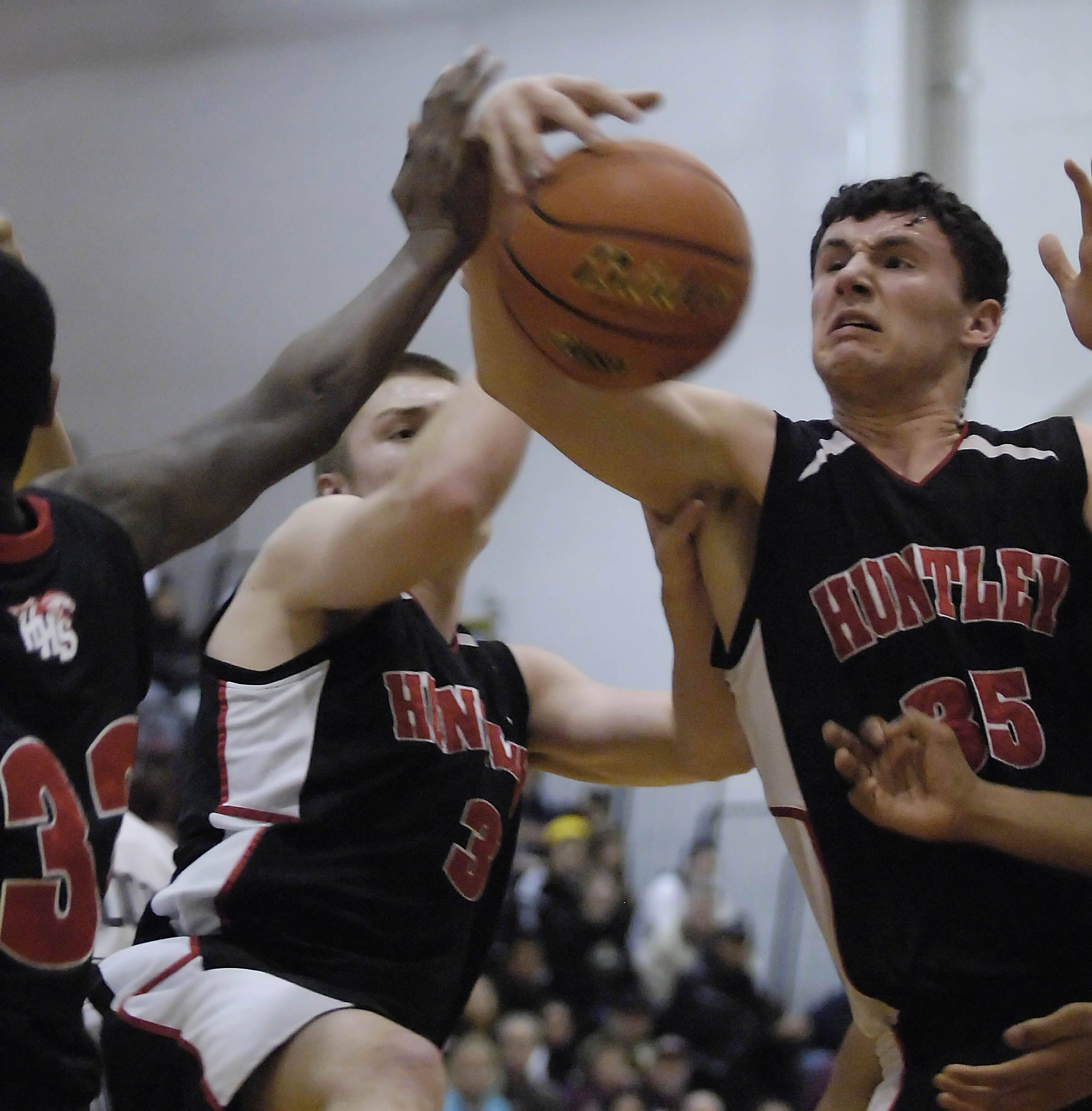 Huntley's Justin Fredrick, right, Tyler Brunschon and Amanze Egekeze, left, dominate the rebound against Elgin in the Jacobs sectional semifinal game Tuesday in Algonquin.