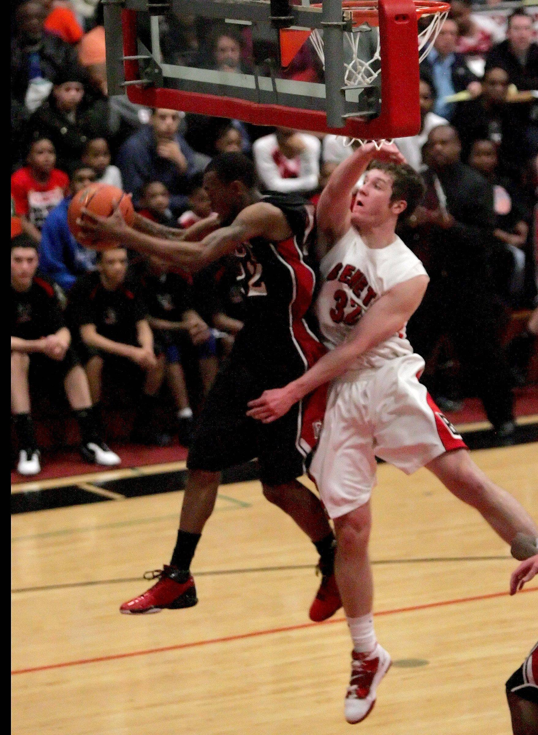 Ryan Boatright of East Aurora, left, grabs a rebound away from Pat McInerney of Benet Academy.