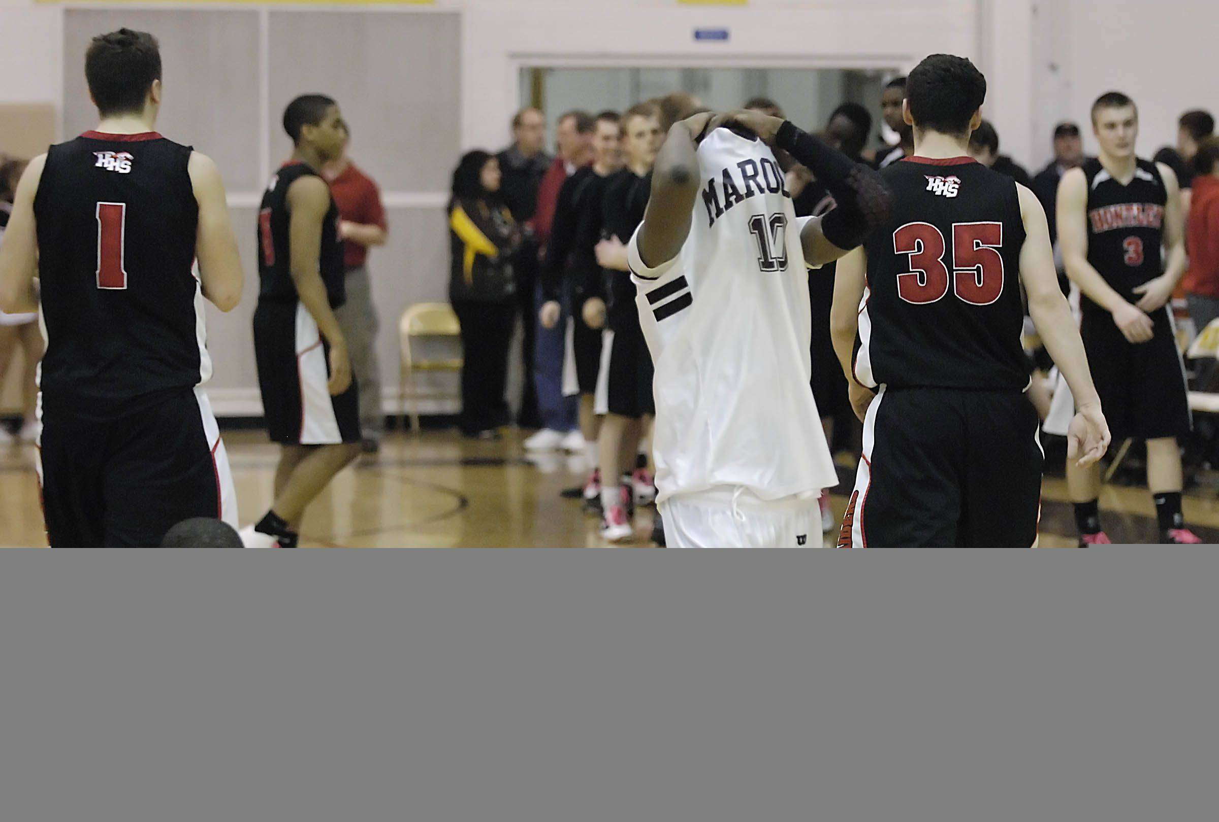Elgin's Cortez Scott, left, and Arie Williams react as Huntley walks off the floor.
