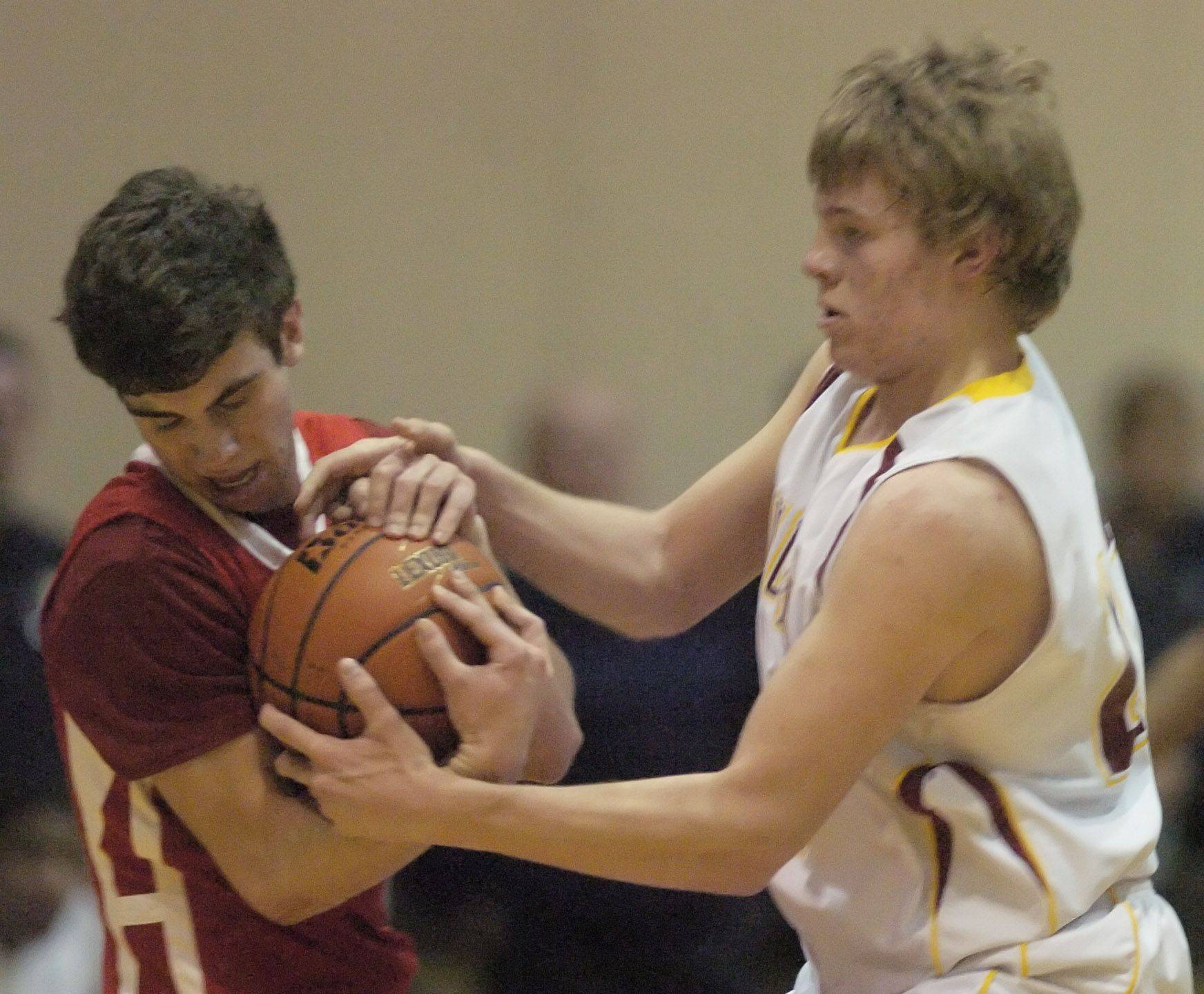 Schaumburg's Kyle Bolger, right, tries to grab the ball from Niles West's Nathan Sagett during Wednesday's sectional semifinal at New Trier.