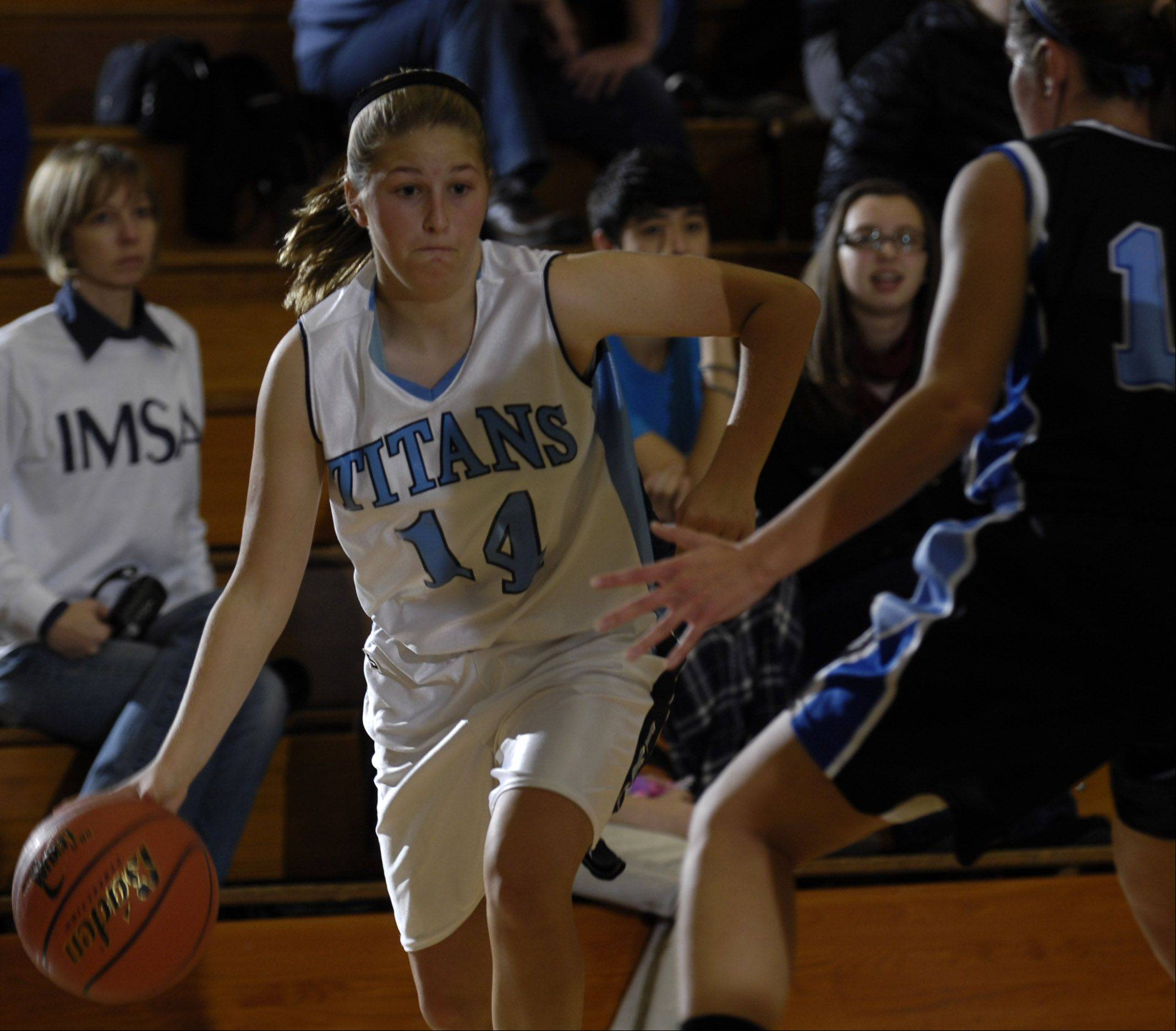 IMSA's Rae Hohle drives past Rosary's Emmy Popovich Monday during their game at IMSA.