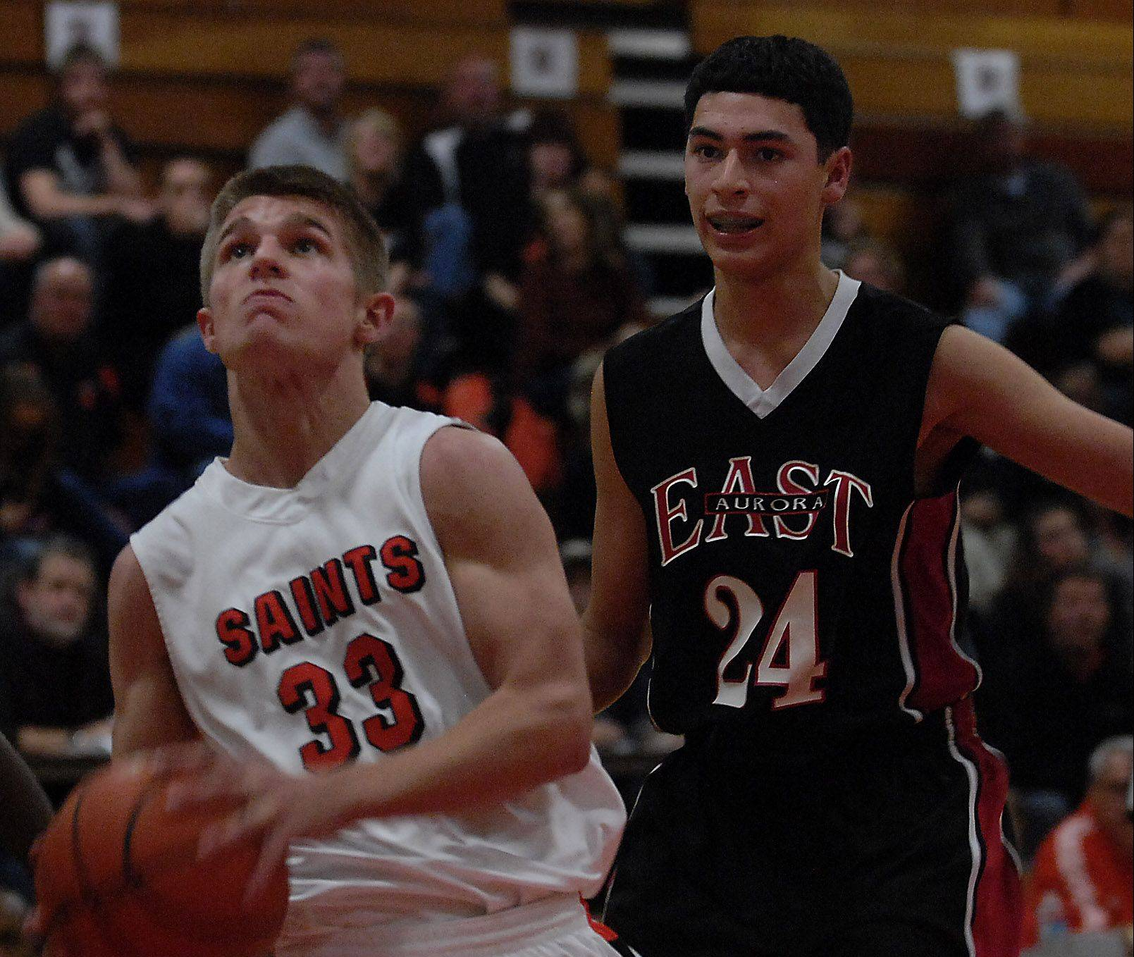 St. Charles East's Brent Kage drives to the basket with East Aurora's Jonathan Villezcas defending during the Saints' 64-34 victory Monday in St. Charles.