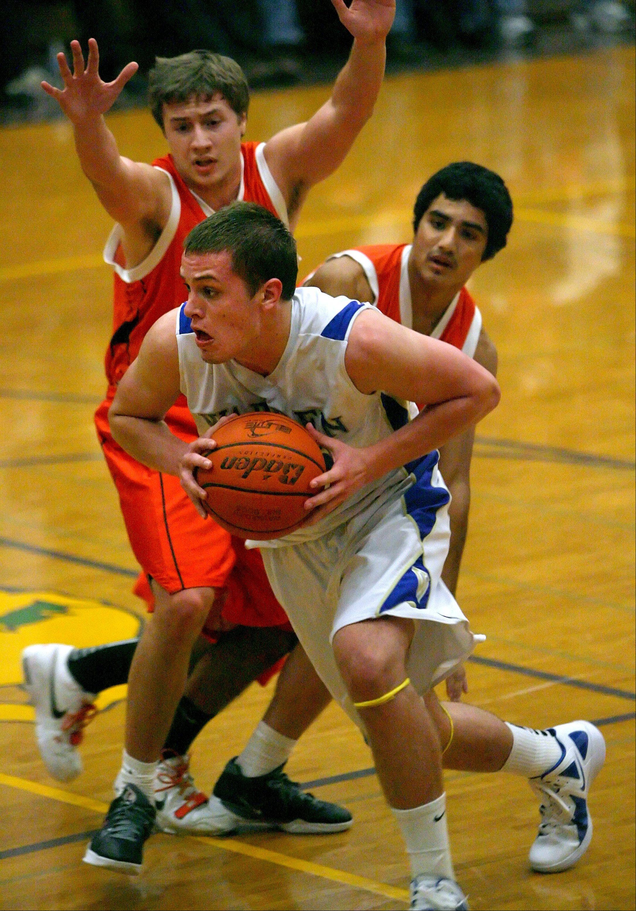 Warren's Jon Geske drives on Lake Forest Academy's Tommy Merritt on Wednesday night at Waukegan High School.