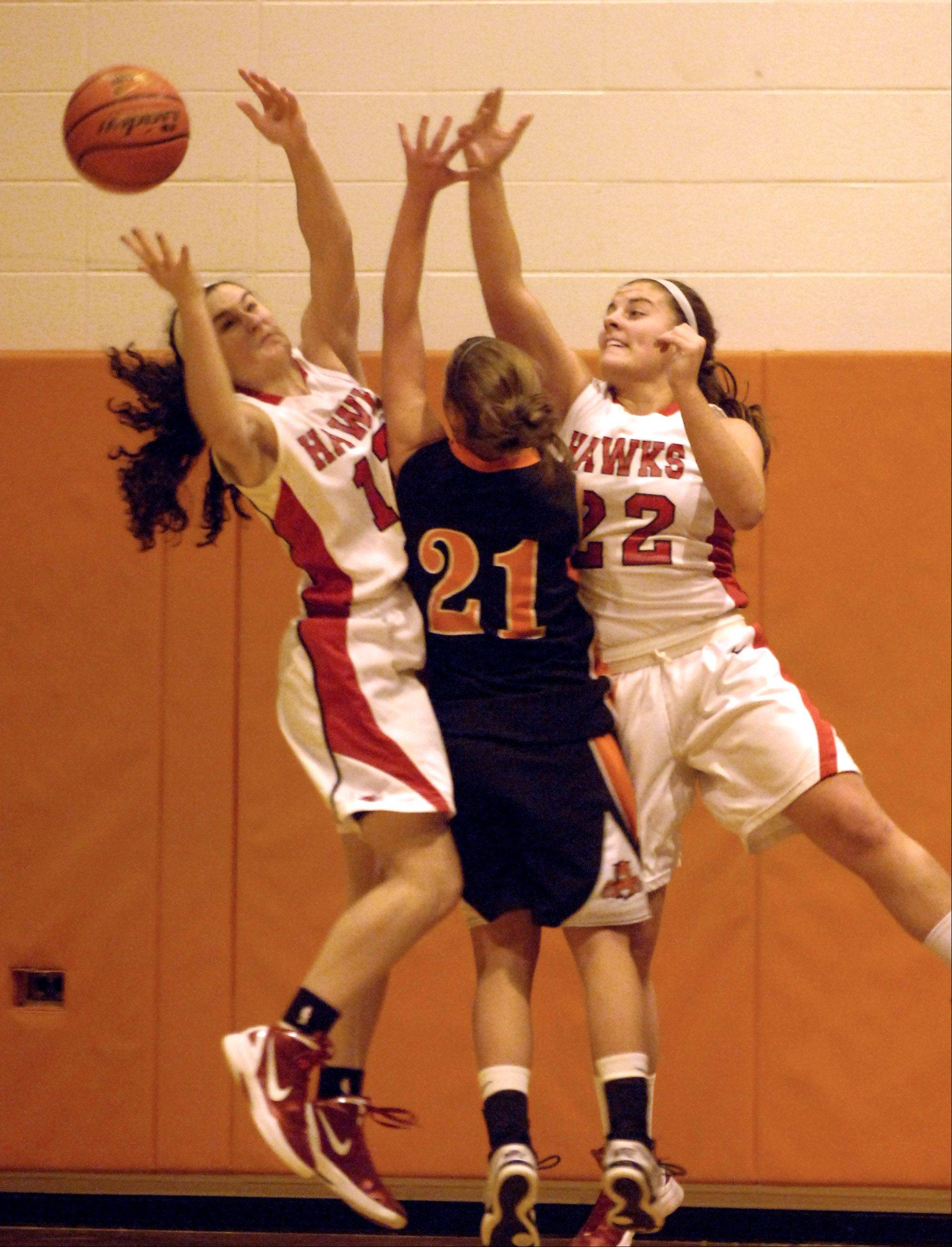 Libertyville's Olivia Mayer (21) reaches for a rebound with Maine South's Regan Carmichael, left, and Nina Duric during tournament play Friday at Buffalo Grove.