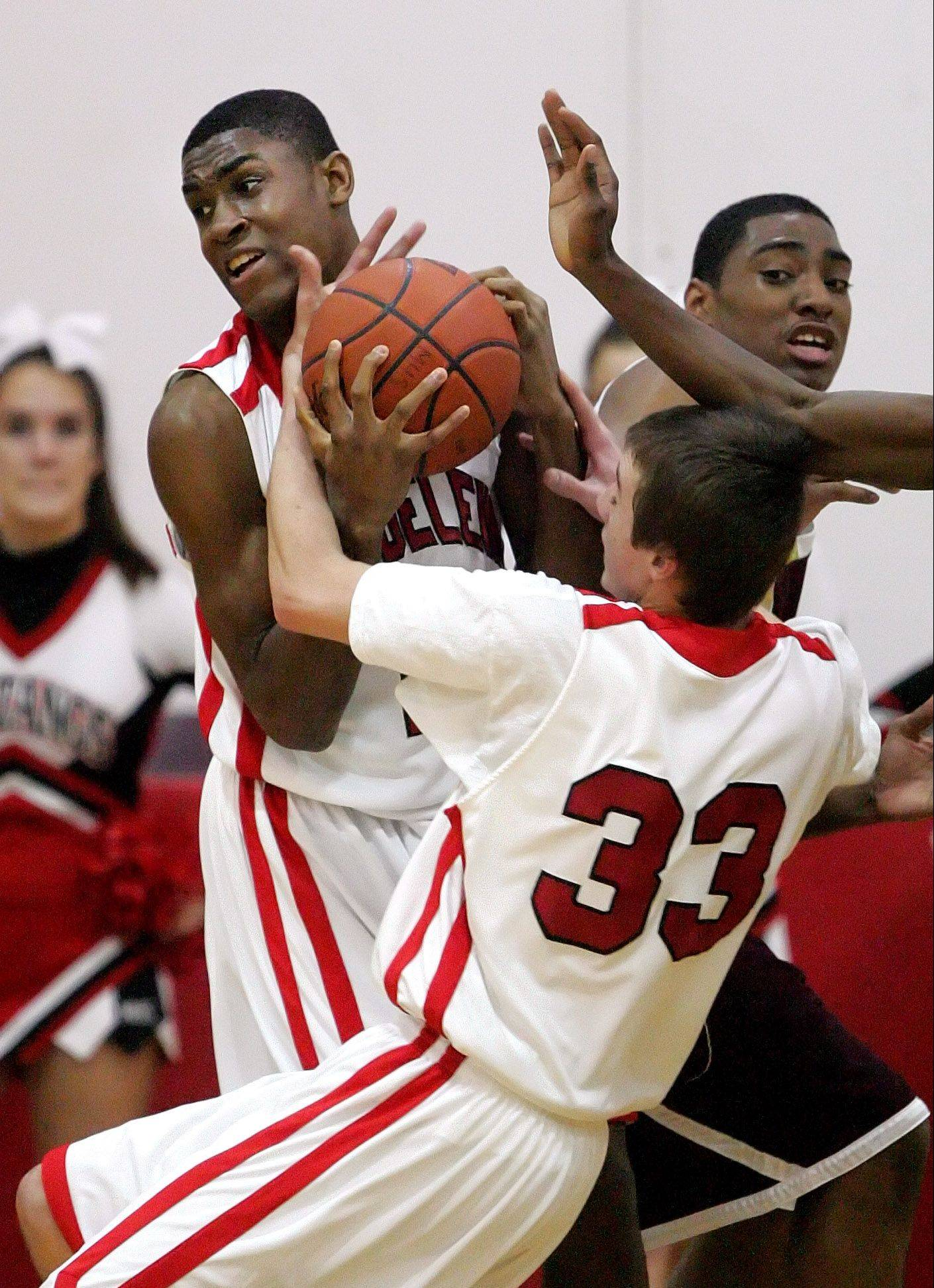 Mundelein's Chino Ebube, left, and Sean O'Brien battle for a rebound with Uplift's Corey Gonore during tournament play Monday at Mundelein.