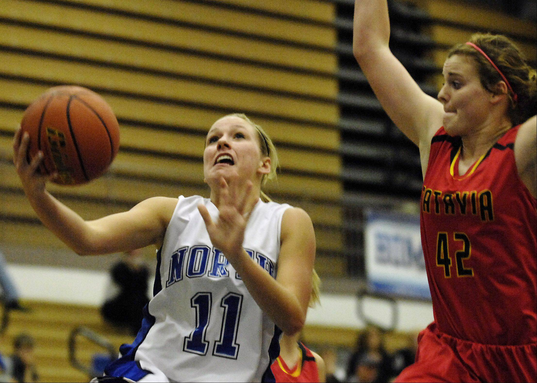 St. Charles North's Megan Booe drives to the basket with Batavia's Katie Ryan defending.