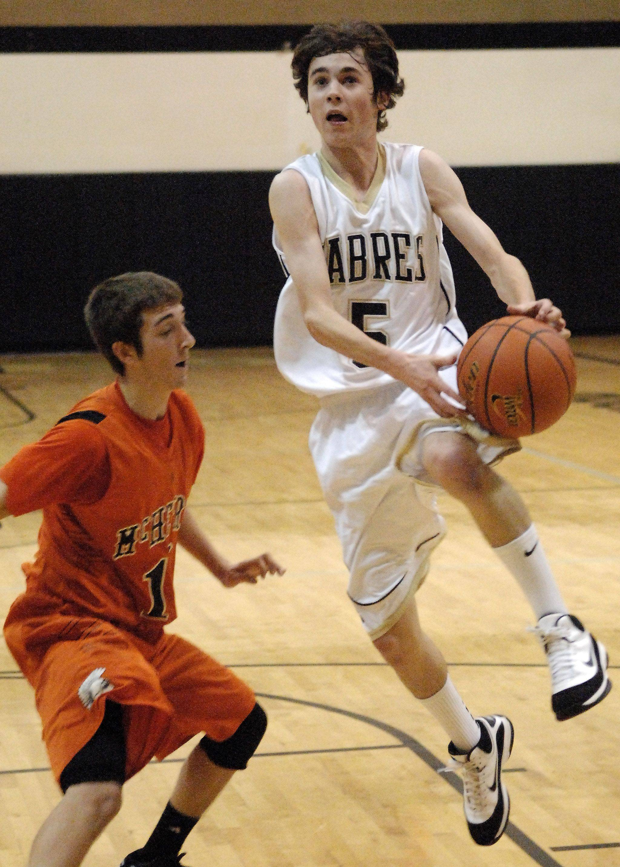 Streamwood's Brent Kiesel drives to the basket past McHenry's Danny Glick during Thursday's game at Streamwood.
