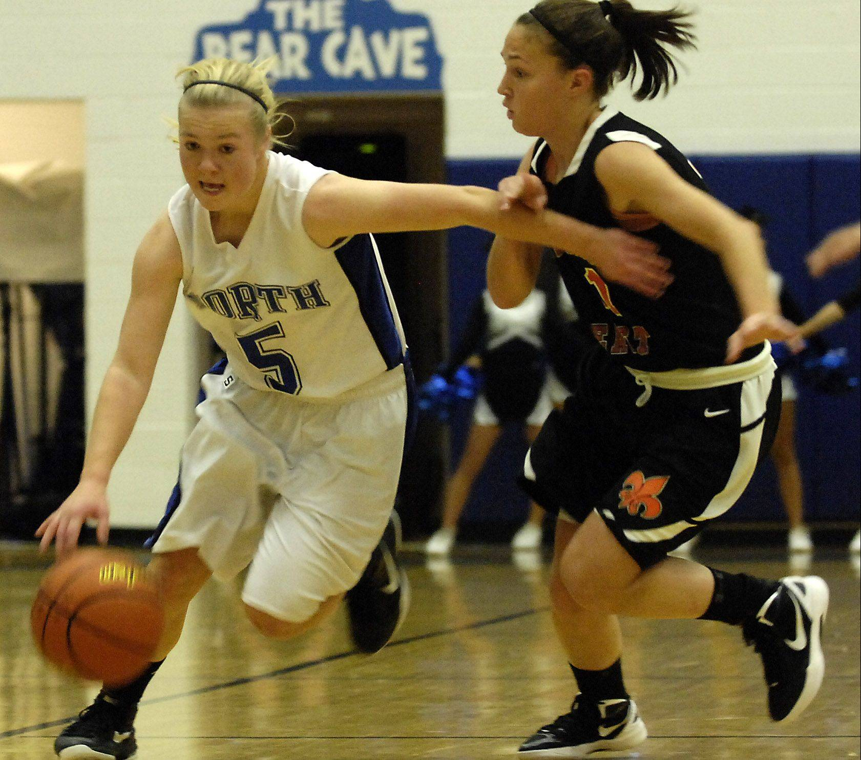 St. Charles North's Natalie Winkates drives against St. Charles East's Carly Pottle Wednesday in St. Charles.
