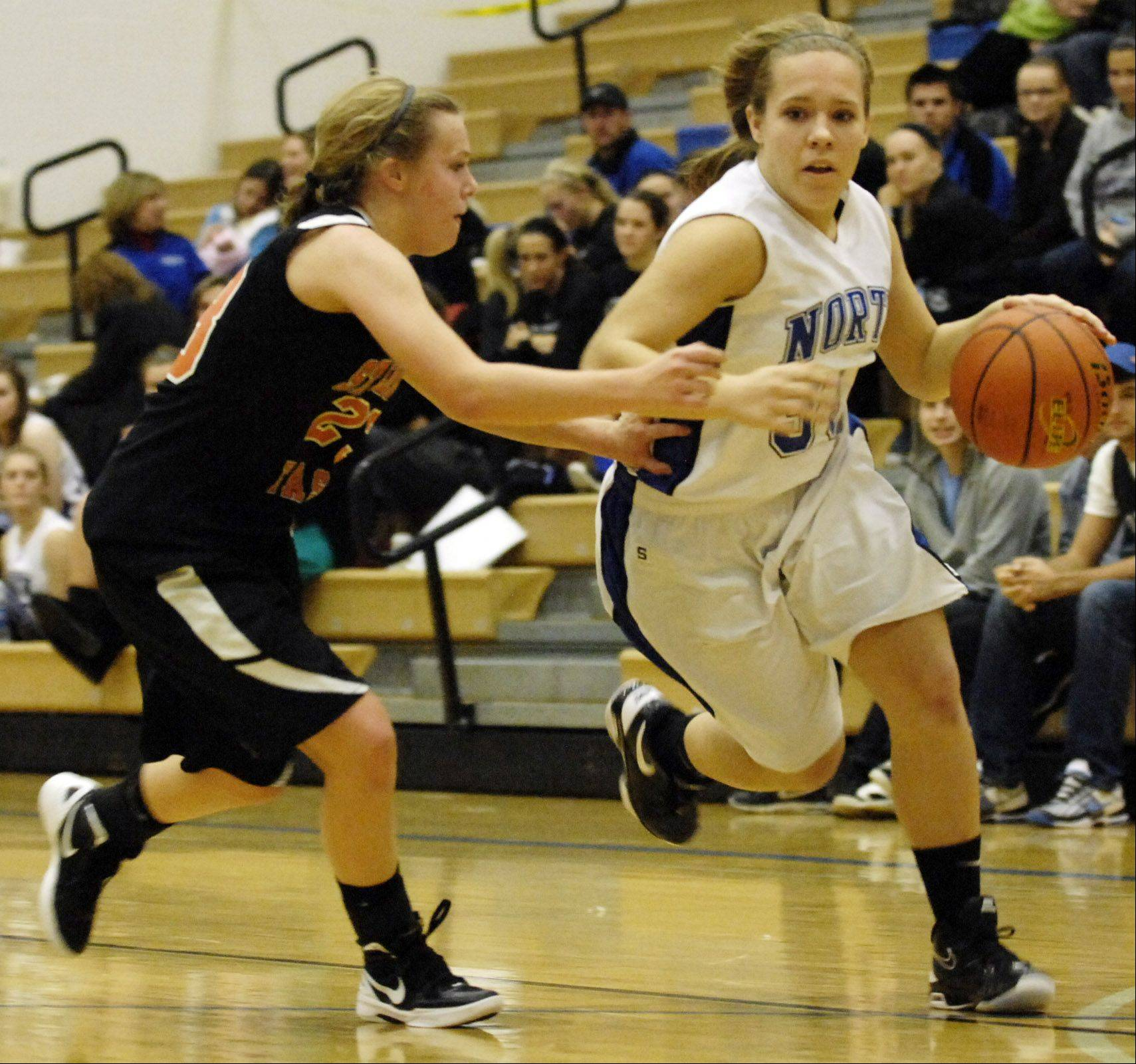 St. Charles North's Ava Tarka drives past St. Charles East's Amanda Hilton during their game Wednesday in St. Charles.