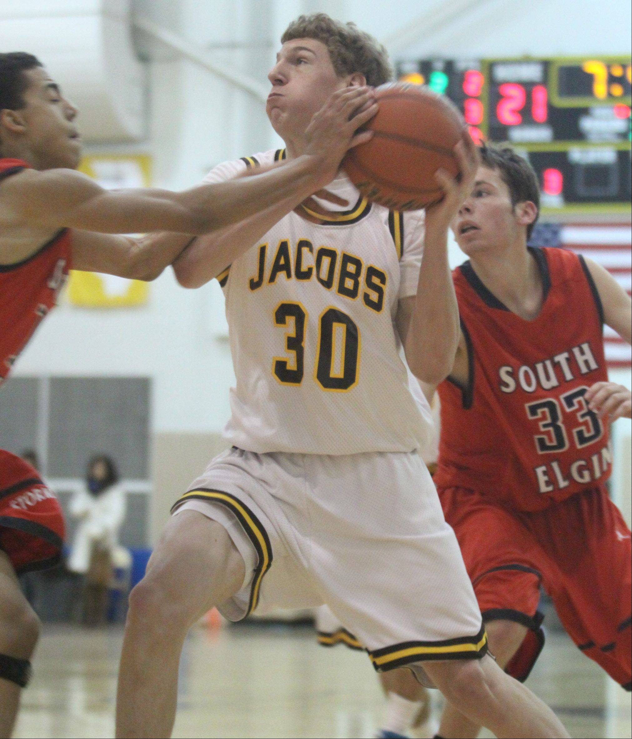 Jacobs' Will Schwerdtmann, center, brings the ball to the hoop against South Elgin's Darius Wells, left, and Eric Stazy, right, during a varsity basketball game in Algonquin on Thursday night. Jacobs hosts its annual Christmas tournament beginning Saturday, while South Elgin plays at York's Jack Tosh tournament Dec. 27-30.